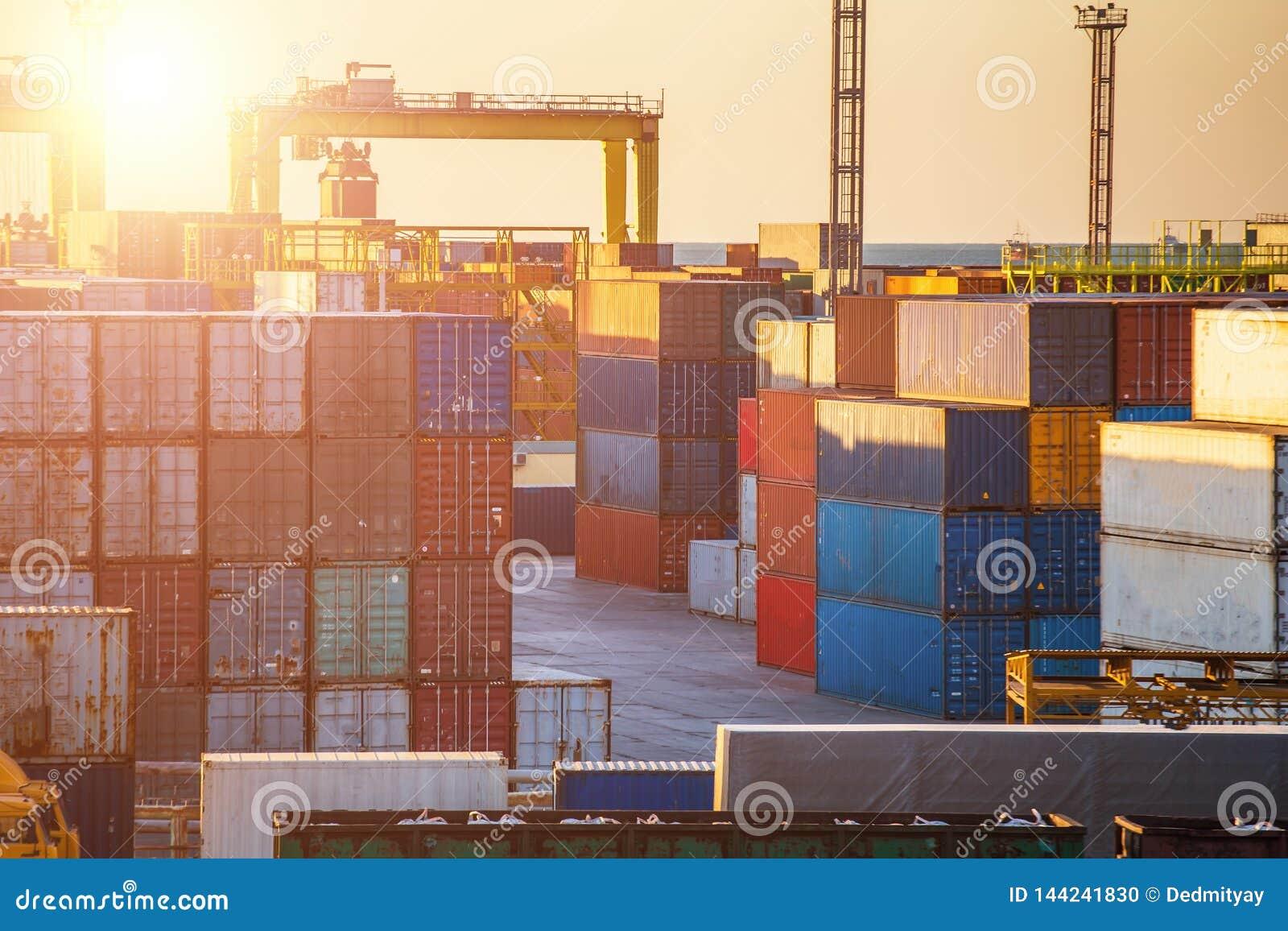 Behållareaskar i lastfraktskepp och industriella portkranar på solnedgången Logistiska havstrans. och sändnings eller leverans
