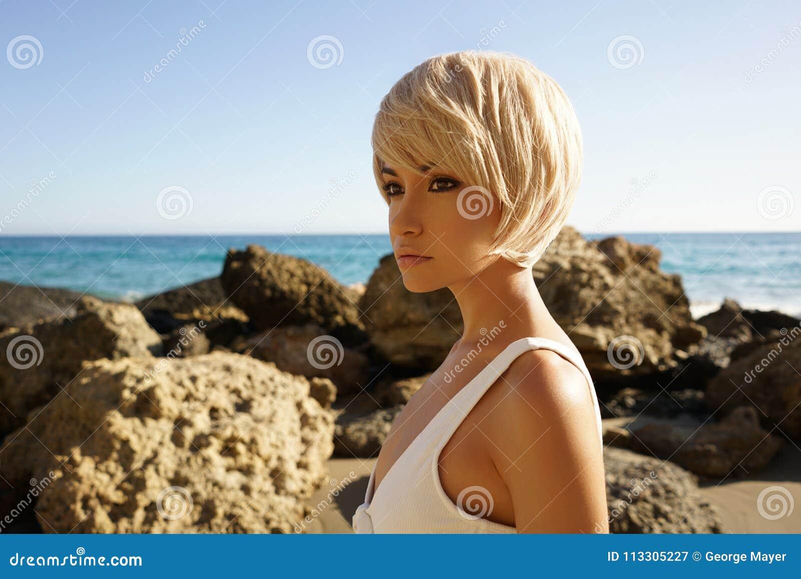 Behagfull kvinna i vit swimwear på stranden