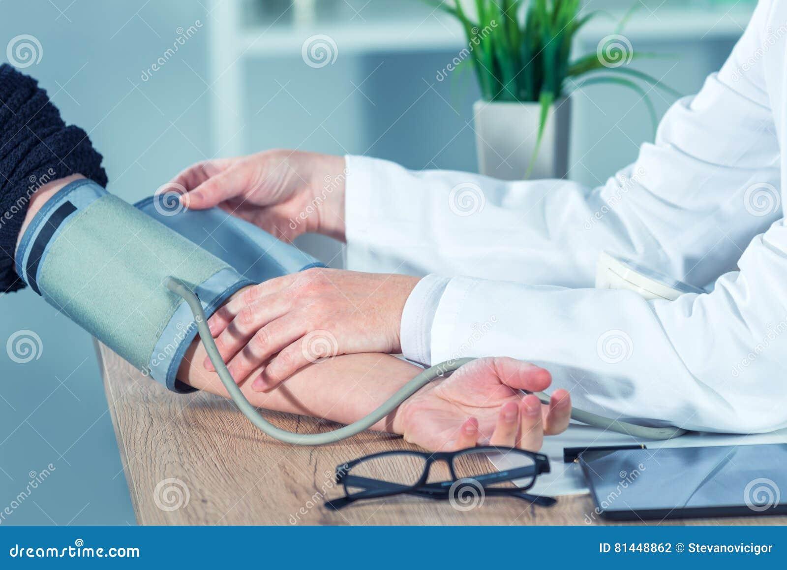 Behandeln Sie messenden Blutdruck des Kardiologen des weiblichen Patienten