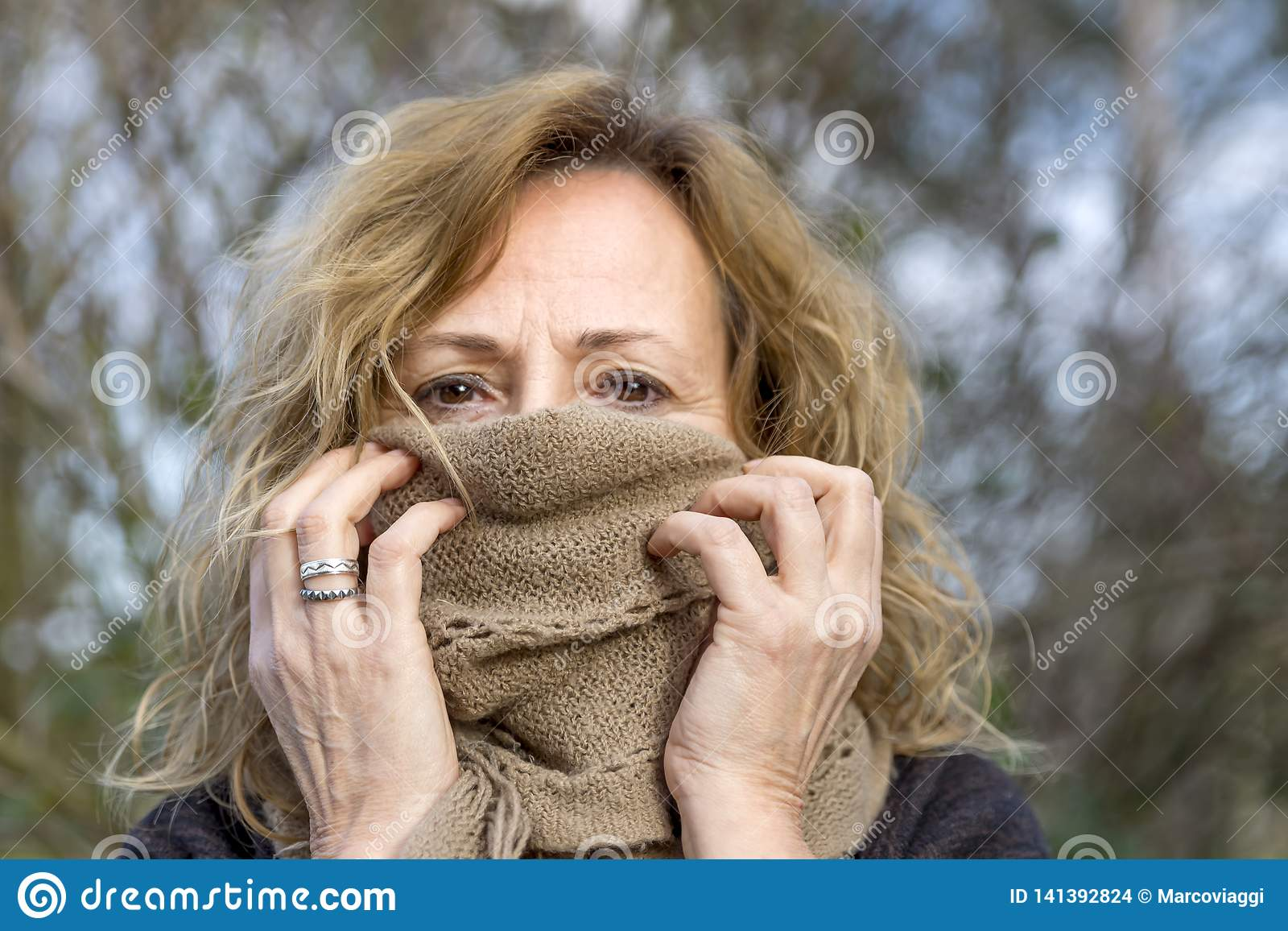 Behandelt de blonde witte vrouw haar gezicht met een beige wolsjaal verlatend slechts de ogen aan het licht gebracht