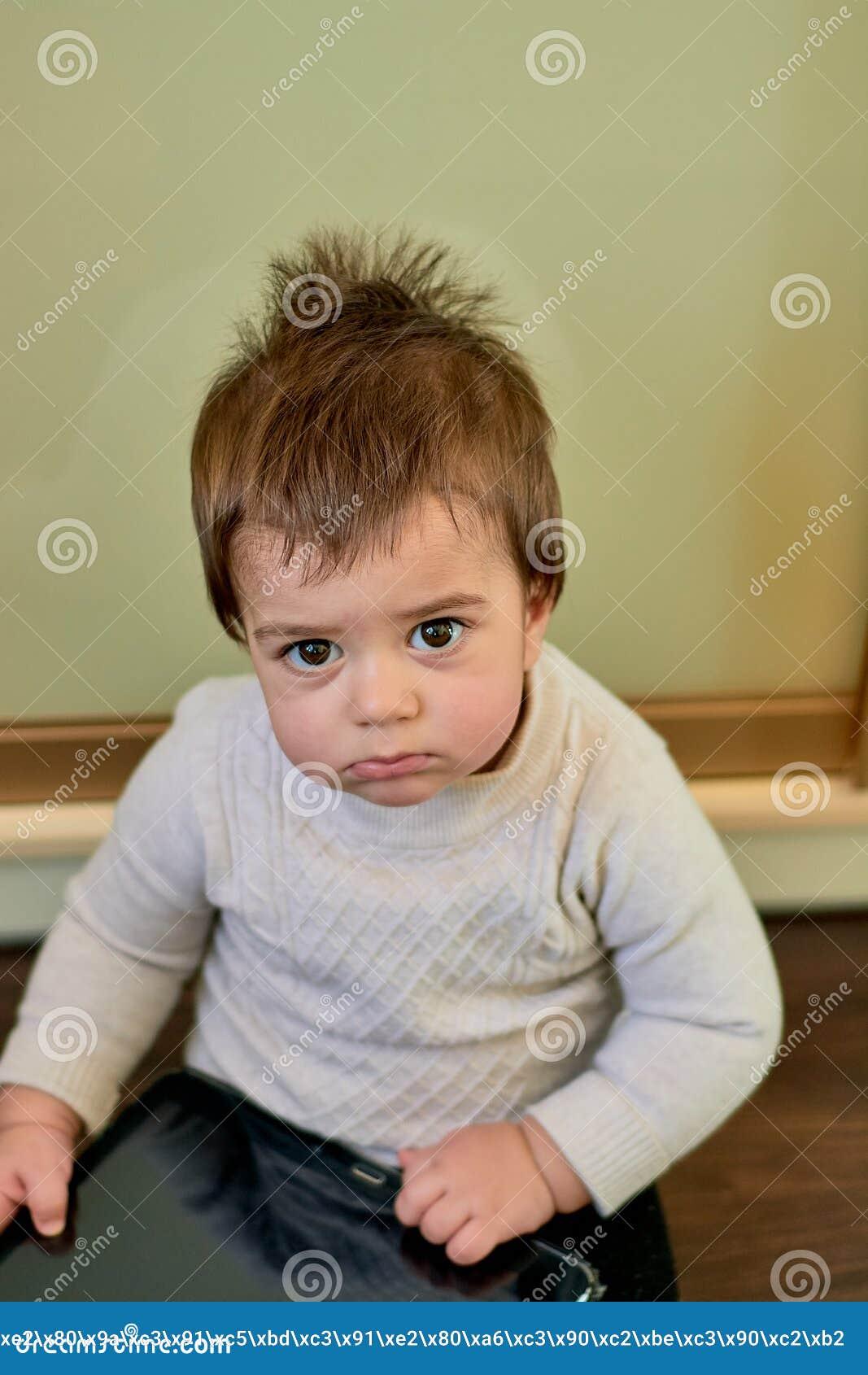 Behandla som ett barn den inomhus ståenden för closeupen av pojken med styggt hår De olika sinnesrörelserna av ett barn