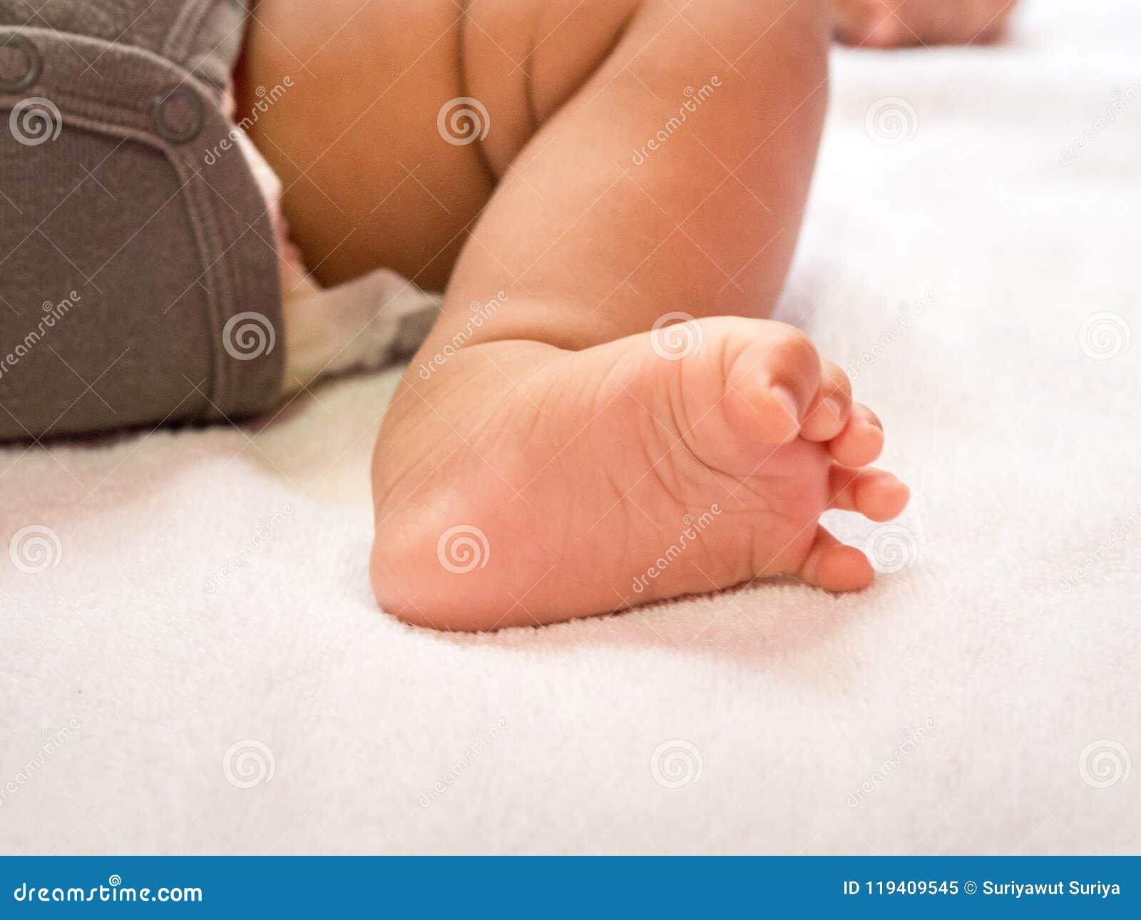Behandla som ett barn den täta foten upp Mycket litet nyfött behandla som ett barn foten lycklig begreppsfamilj