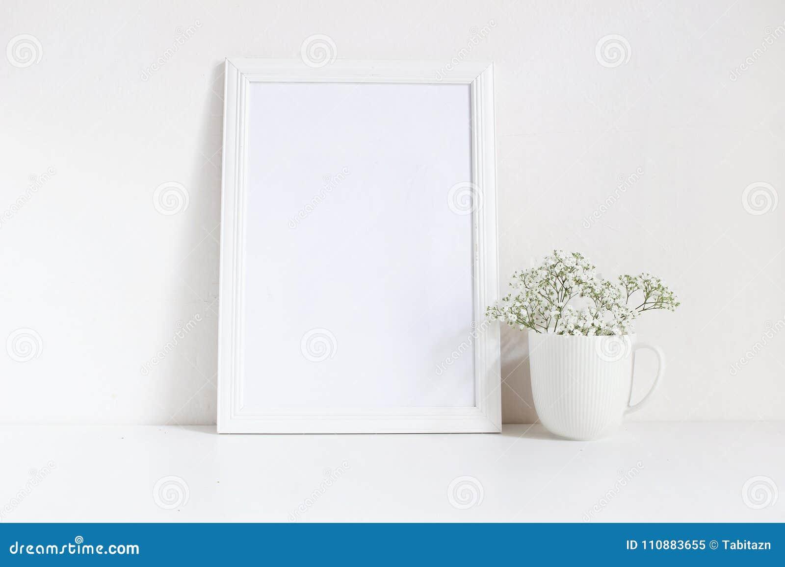 Behandla som ett barn den tomma trärammodellen för vit med andedräkt, Gypsophila som blommor i porslin rånar på tabellen Affischp