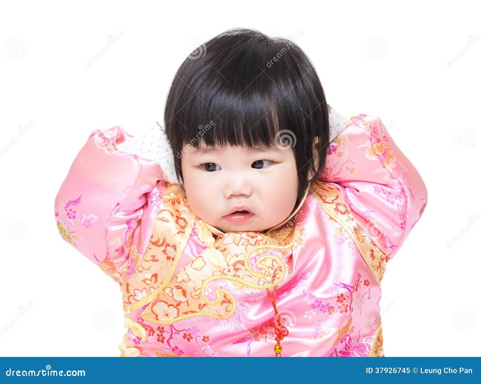 Behandla som ett barn det rörande huvudet för flickan med dräkten för traditionell kines