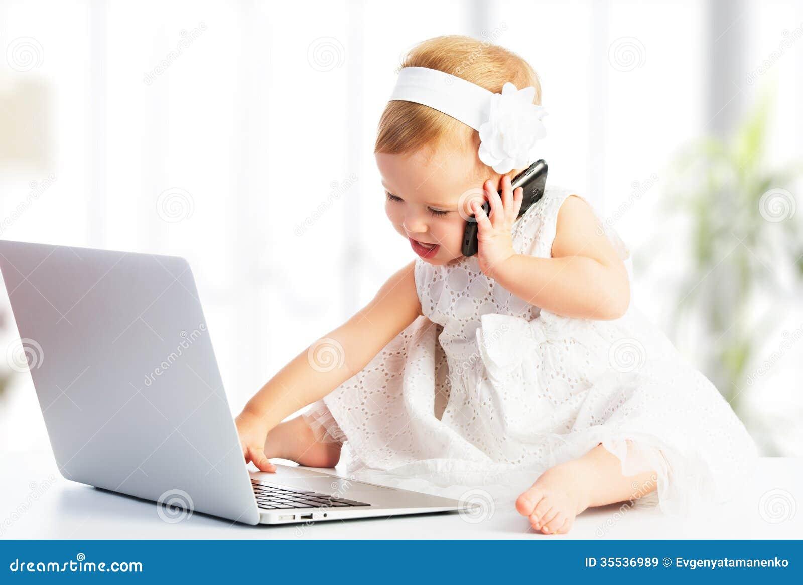 Behandla som ett barn flickan med datorbärbara datorn, mobiltelefon