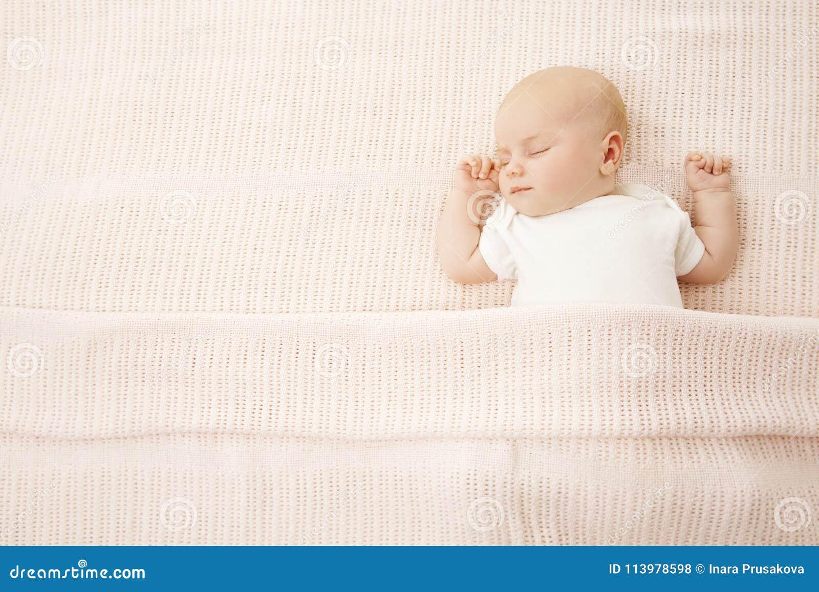 Behandla som ett barn flickasömn i säng, täckt stucken filt för nyfött barn