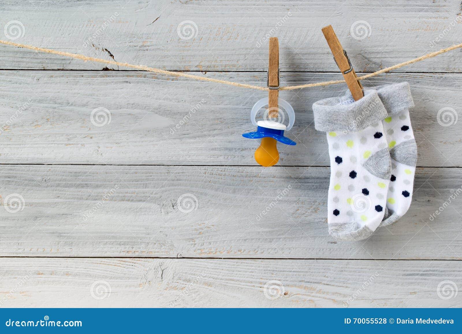 Behandla som ett barn fredsmäklaren och sockor som hänger på klädstreck på träbakgrund