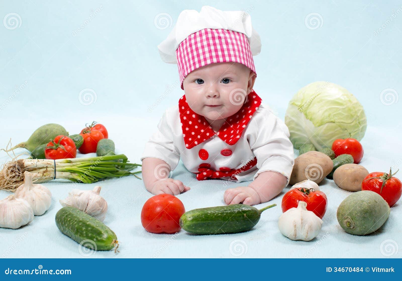 Behandla som ett barn hatten för kocken för kockflickan den bärande med nya grönsaker.