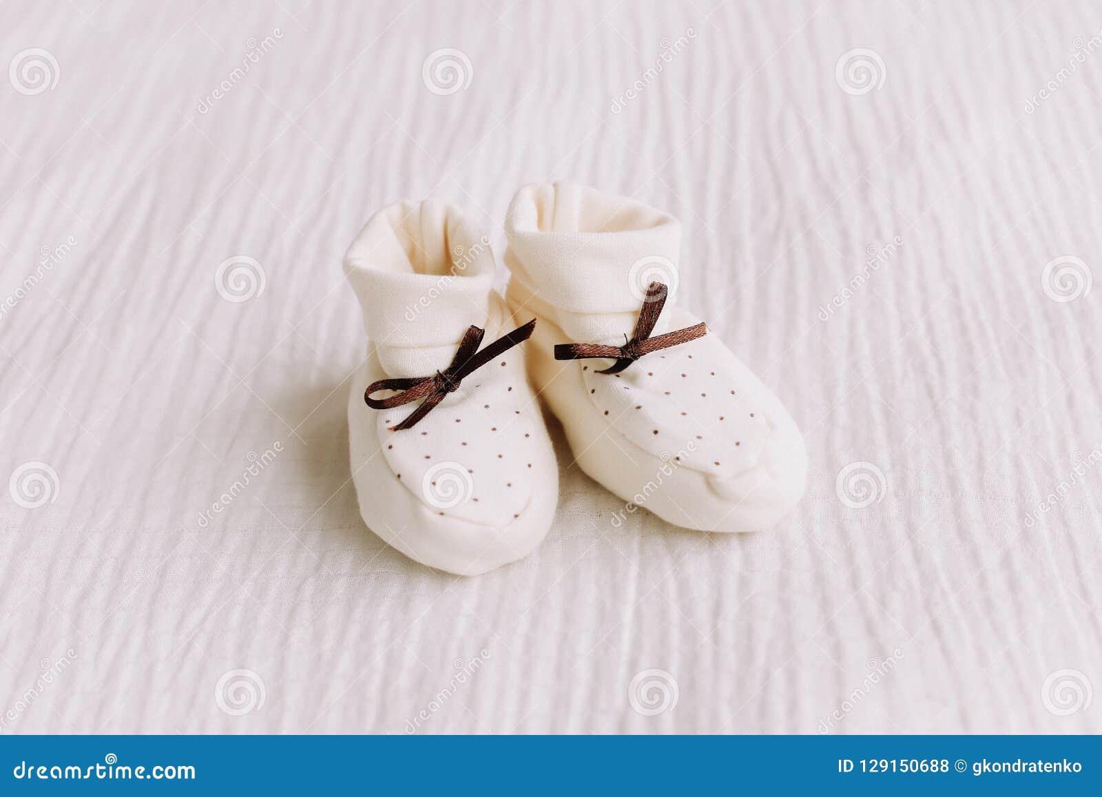 Behandla som ett barn kängor för ` s på vit bakgrund Att vänta på behandla som ett barn vita skor för nyfött på en pastellblåttba