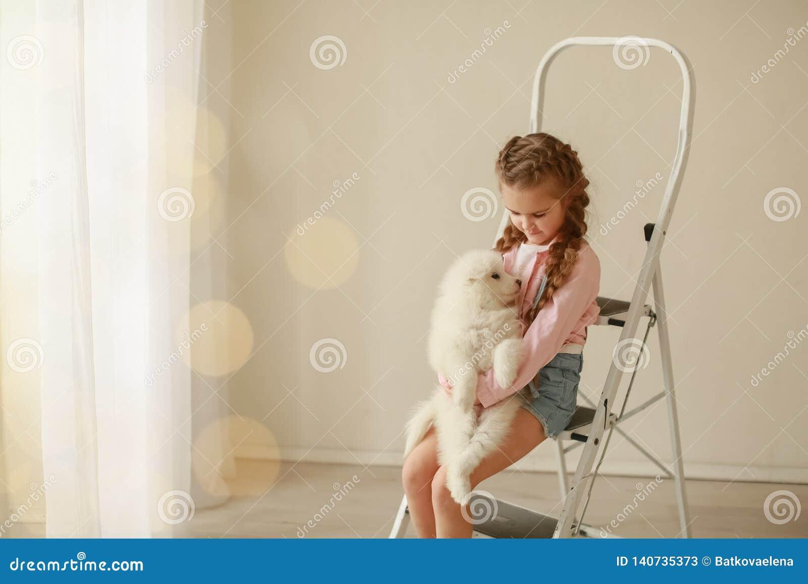 Behandla som ett barn kramar den vita fluffiga valpen ungar