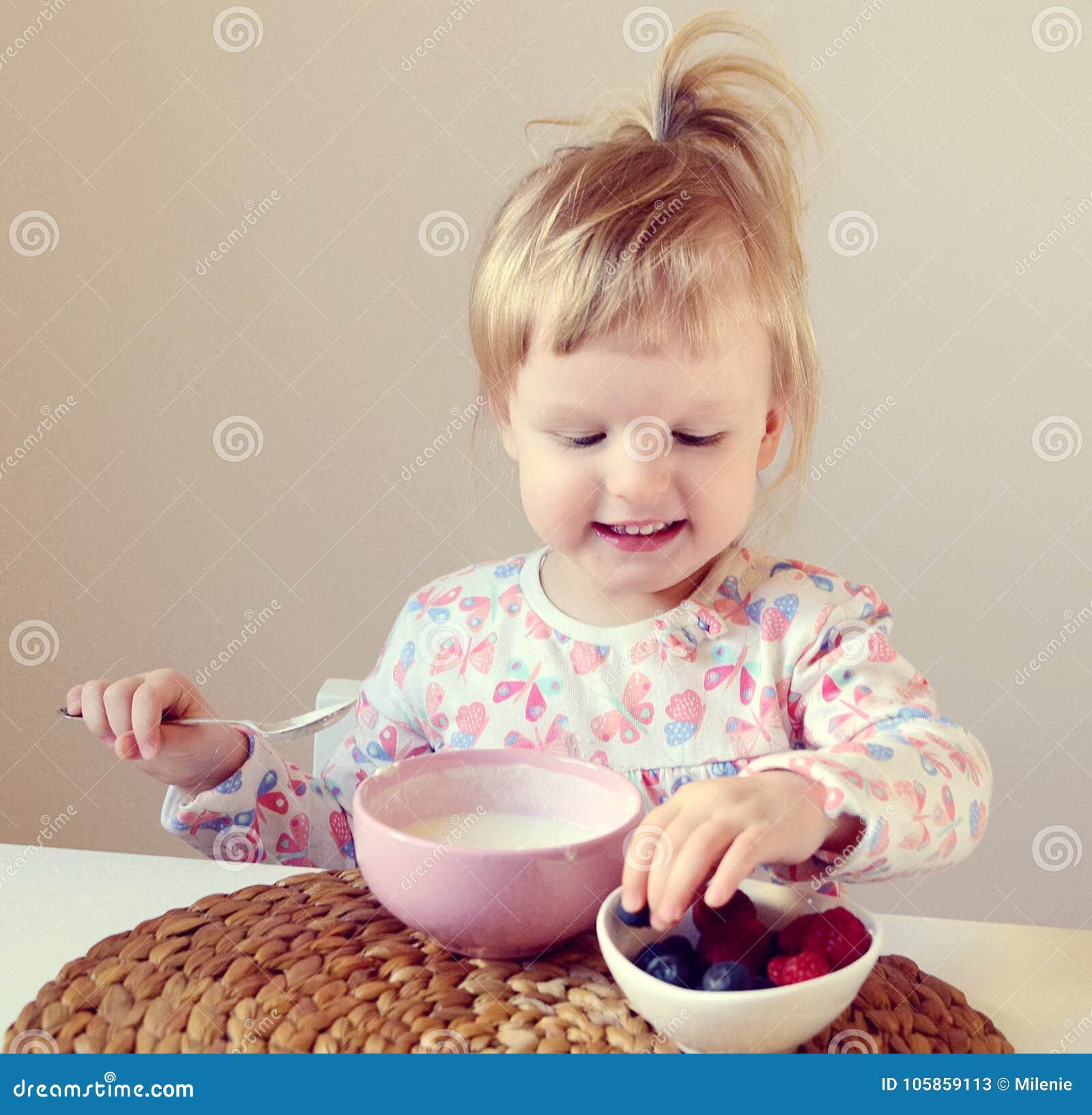 Behandla som ett barn lite flickan som hemma äter den sunda frukosten, bär och yoghurt