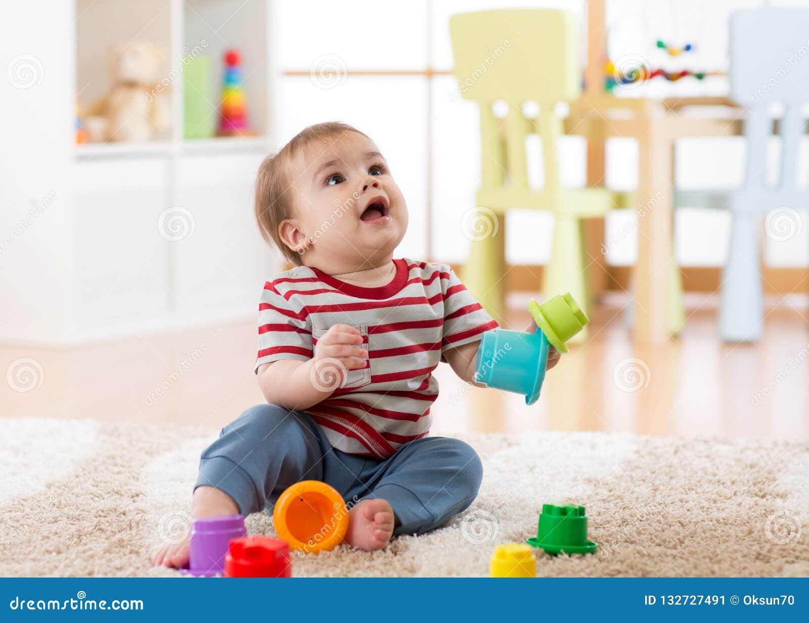 Behandla som ett barn litet barnpojken som inomhus spelar med utvecklings- leksaksammanträde på mjuk matta