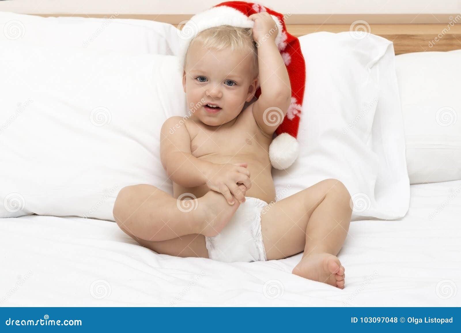 Behandla som ett barn med santa hattsammanträde på en vit soffa Julfilial och klockor