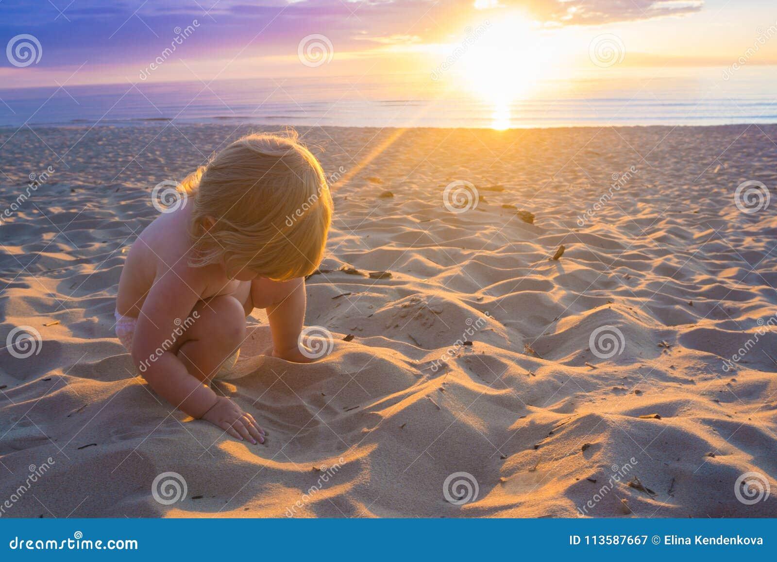 Behandla som ett barn plaing i sand på kusten av det baltiska havet under solnedgång