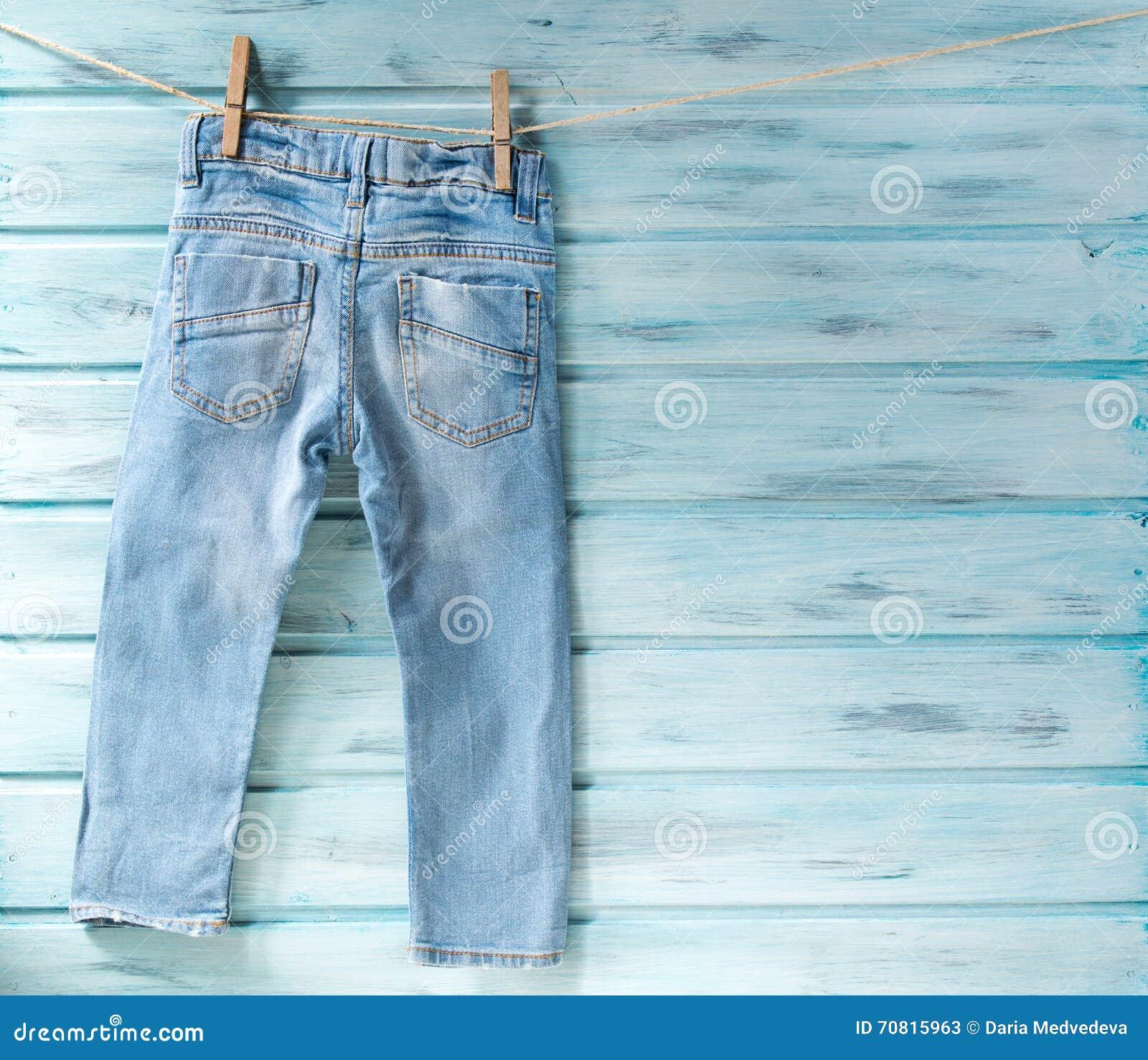 Behandla som ett barn pojkejeans som hänger på en klädstreck på blå träbakgrund