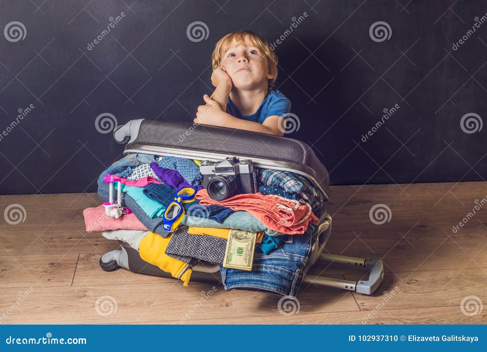 Behandla som ett barn pojken och loppresväskan Unge och bagage som packas för Vacatio