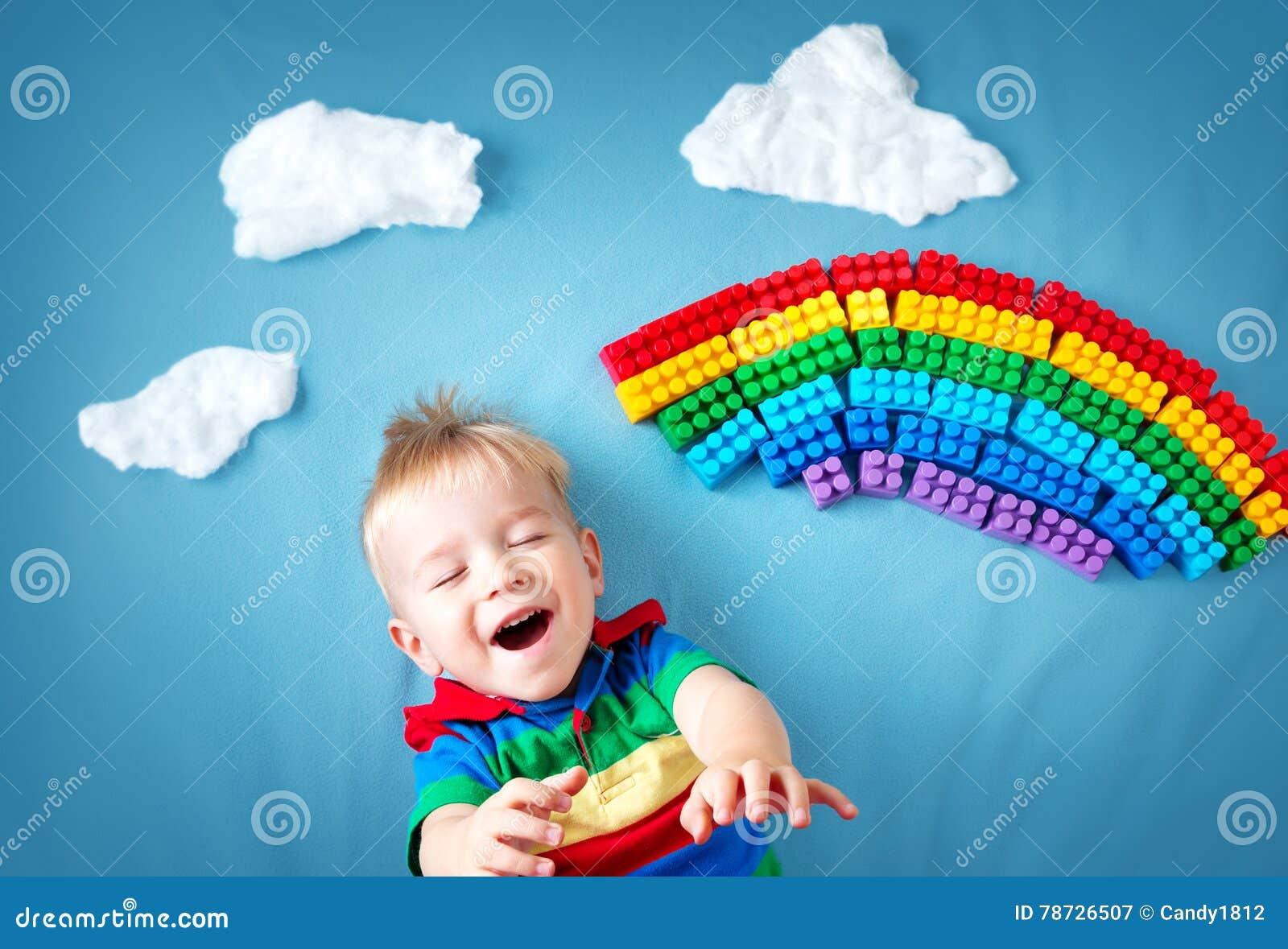 Behandla som ett barn pojken som ligger på filten med regnbågen och moln