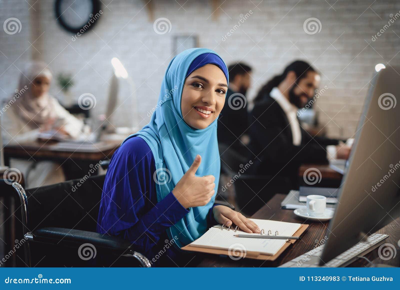 Behinderte arabische Frau im Rollstuhl, der im Büro arbeitet Frau gibt Daumen auf