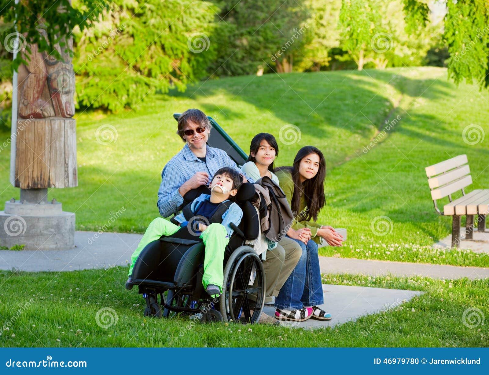Behinderter Junge im Rollstuhl mit Familie draußen am sonnigen Tag sitzen