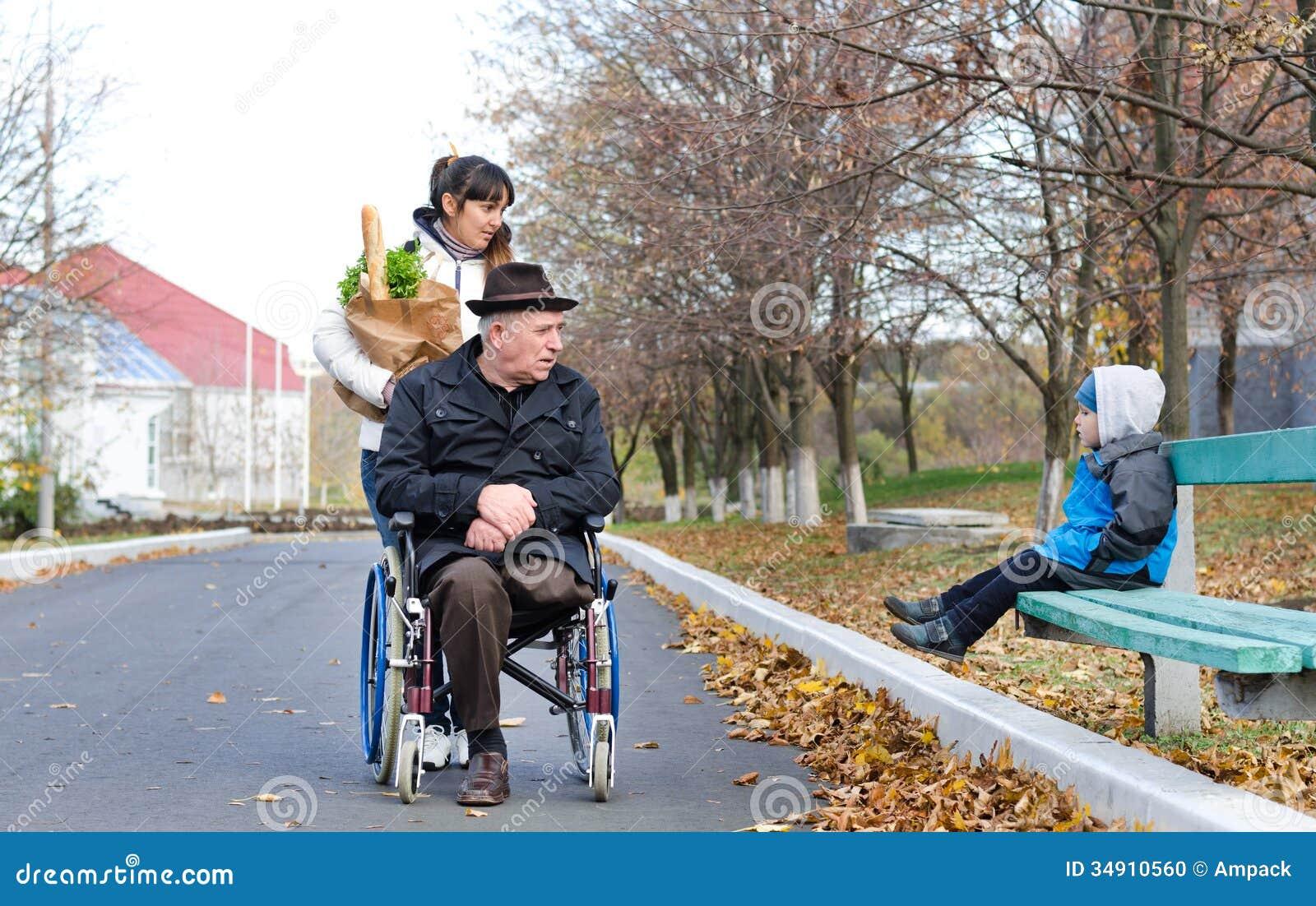 Behinderter Mann und sein Betreuer plaudern zu einem kleinen Jungen