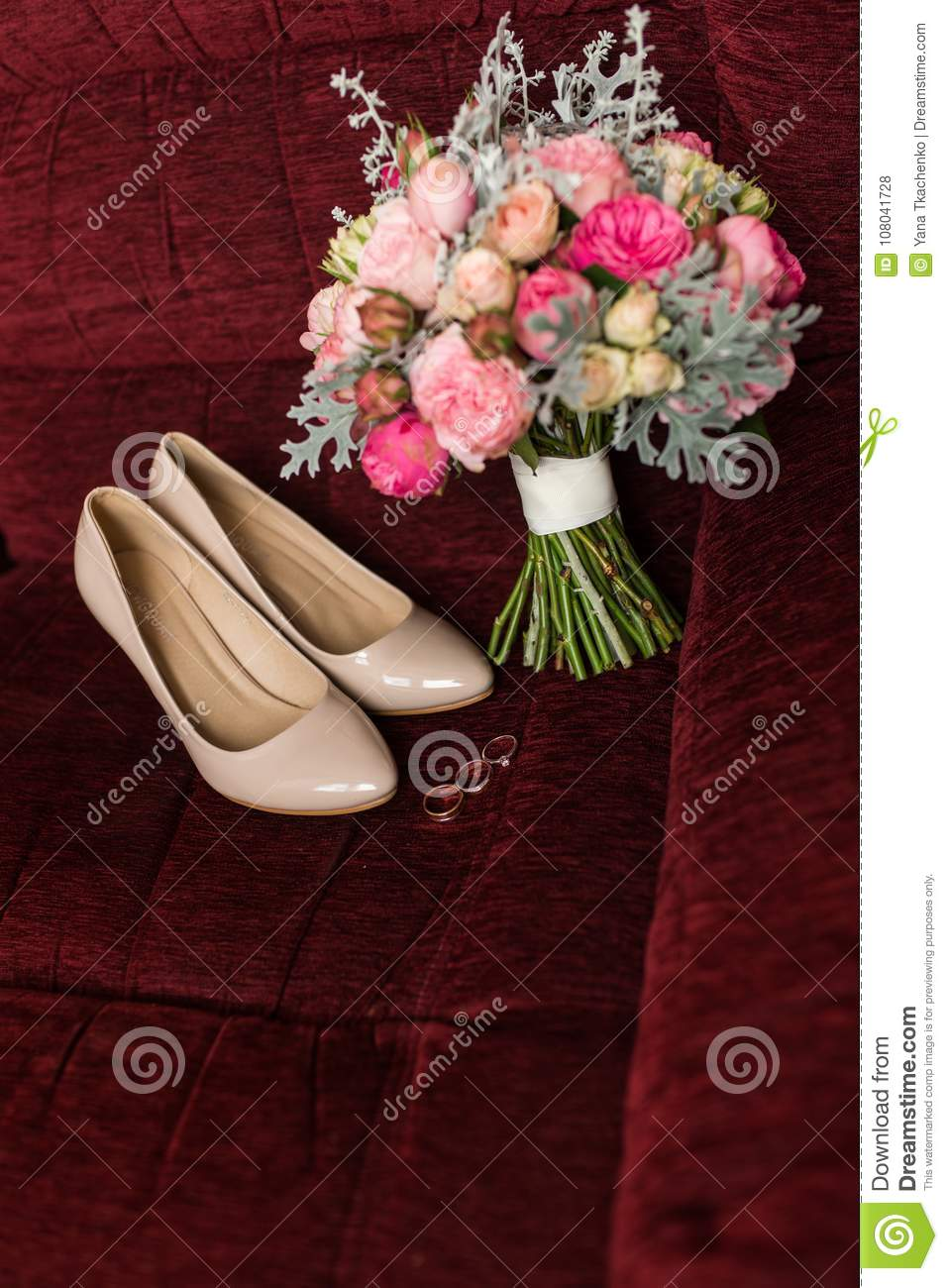 Beige Bridal Shoes And A Wedding Rings Lying On A Red Armchair ...