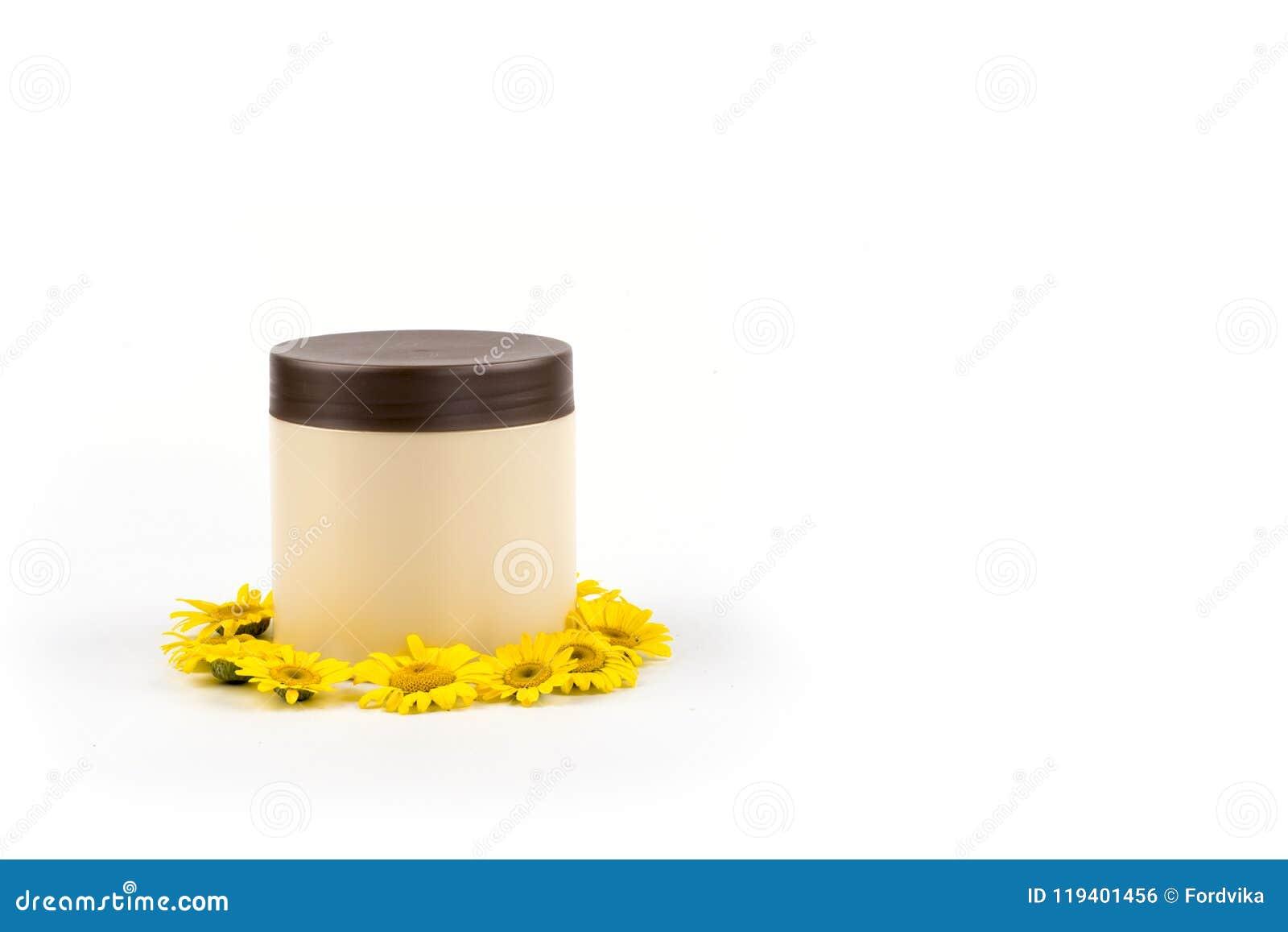Beige kruik met bruin deksel, mocap voor room, balsem, masker en kleine gele madeliefjes op een witte achtergrond