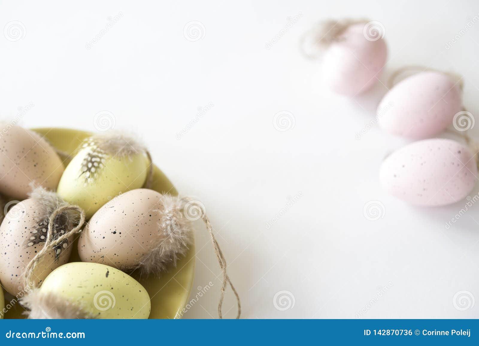 Beige, roze en gele paaseieren op plaat, op witte lijst De ruimte van het exemplaar