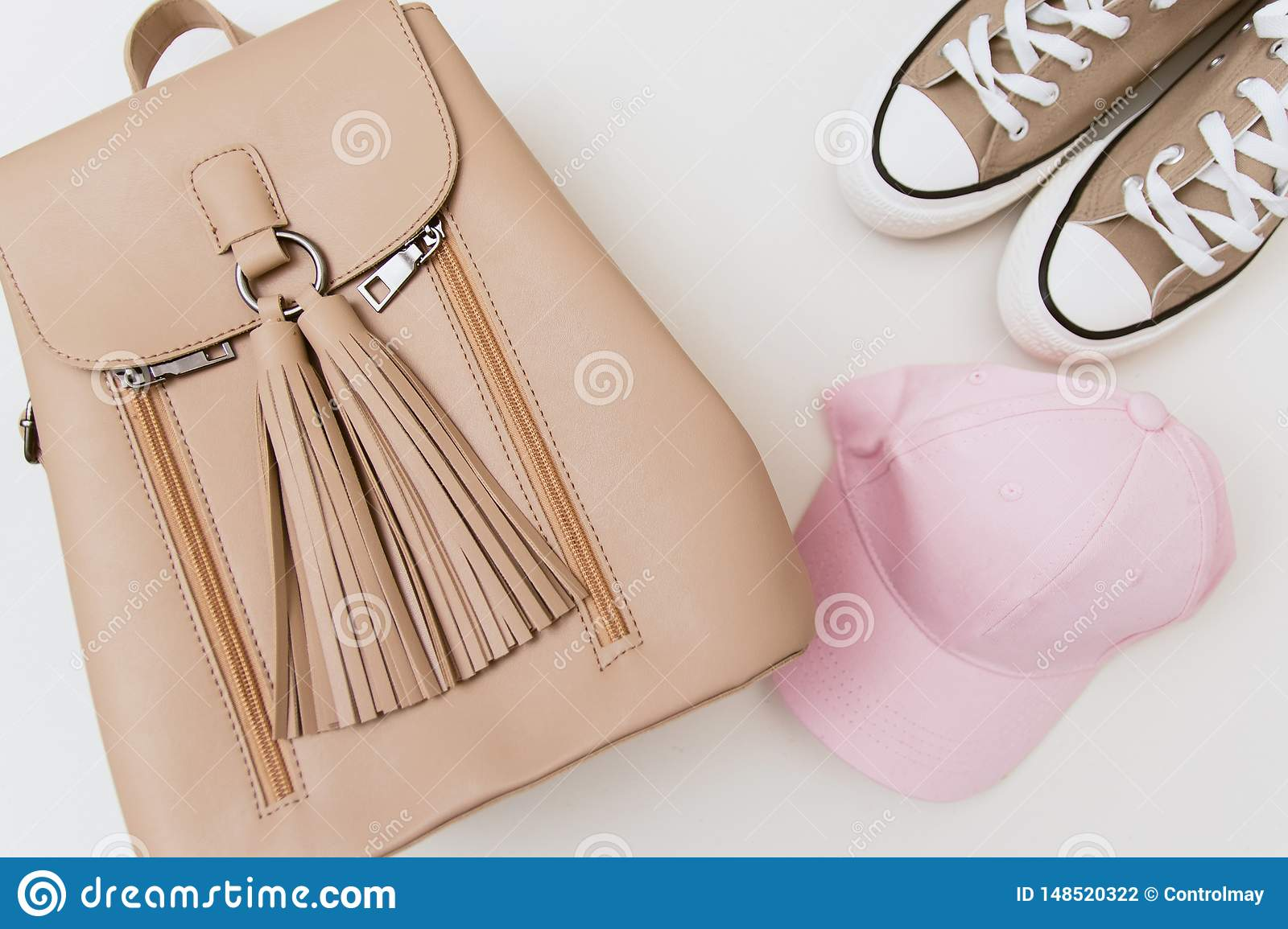 Beige sneakers, backpack and pink cap on pastel light background.