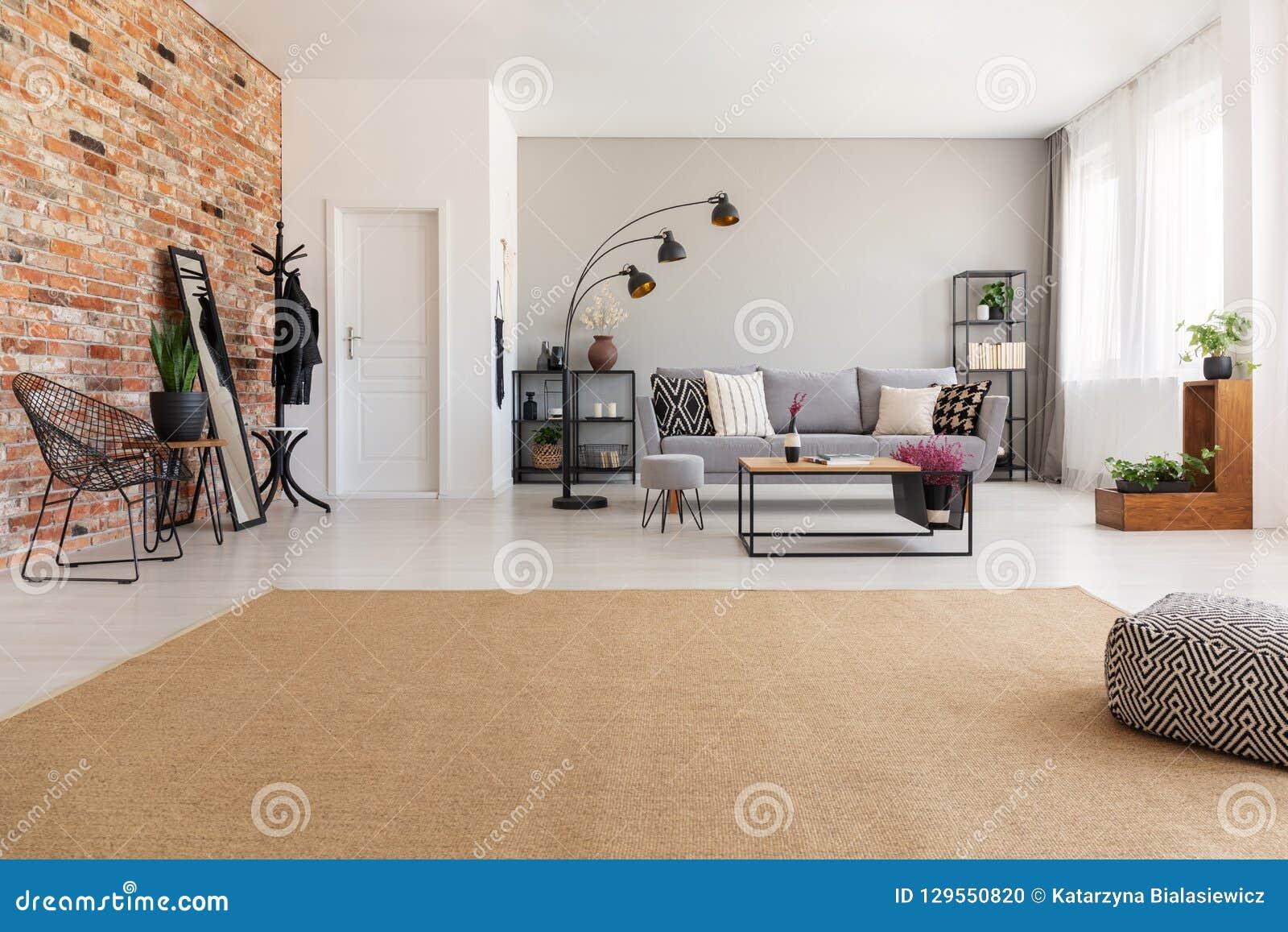 Beige Teppich im modernen Wohnzimmer Innen mit grauer Couch, industrielle schwarze Metalllampe, hölzerner Couchtisch