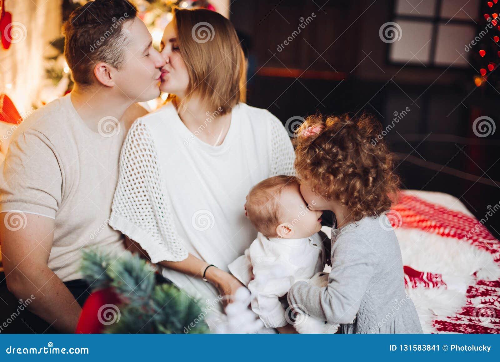 Beijando pais com aperto de crianças no Natal
