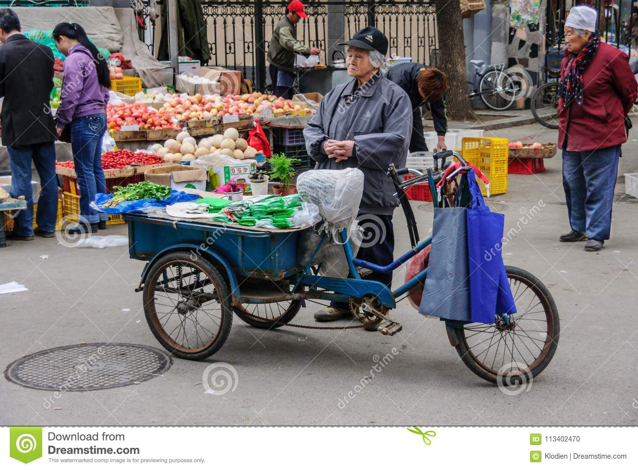 Old Lady Sells Celery Off Blue Tricycle On Market  Editorial Image