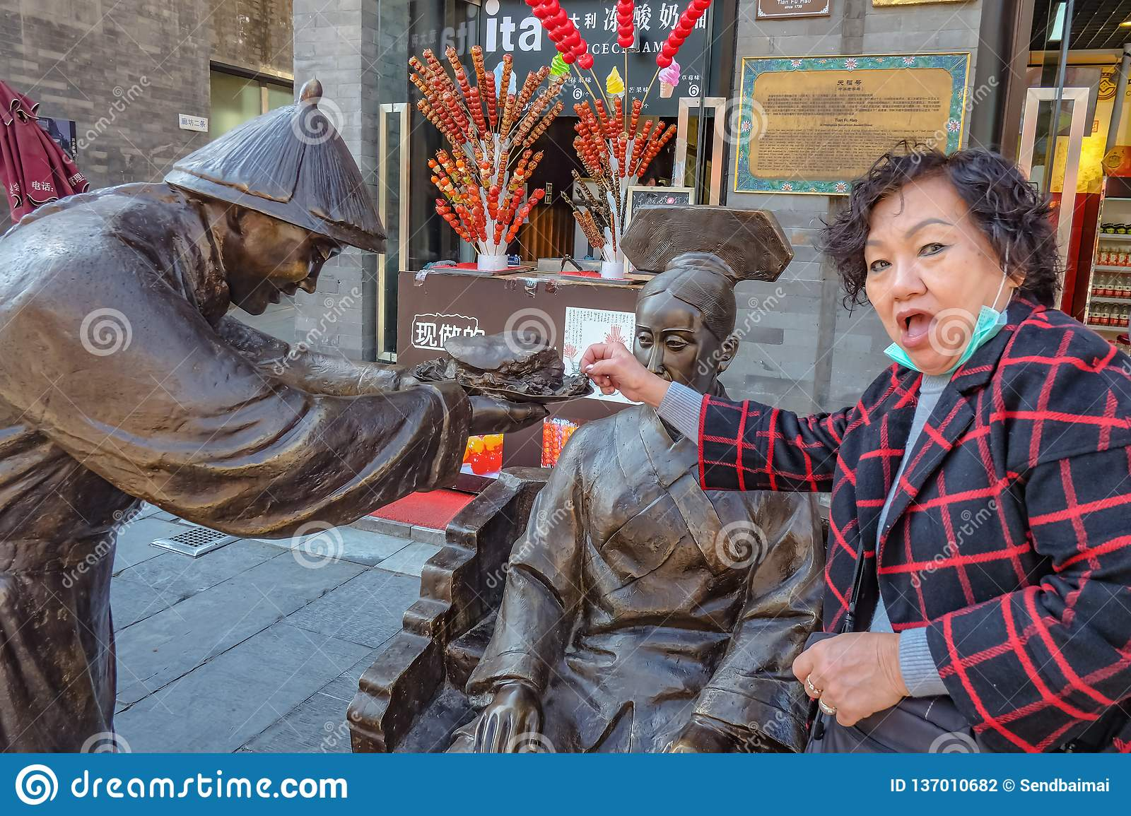 Funny Senior women Try to Steal some Food from Statue of Chinese People give his Food to women on qianmen Street.Qianmen street Th