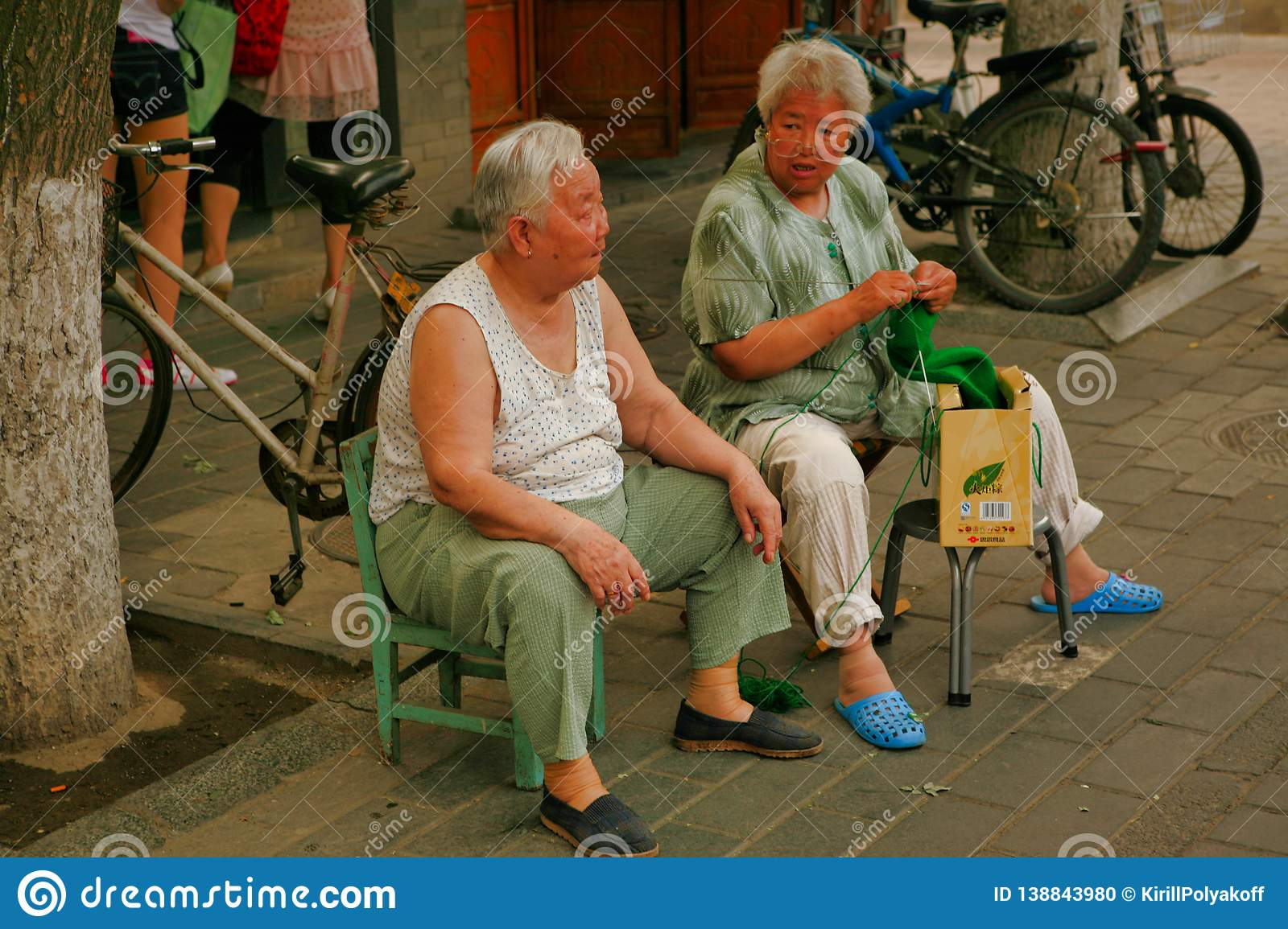 Beijing, China - June 13, 2018: Two elderly Chinese women sit in a street in Beijing and talk.