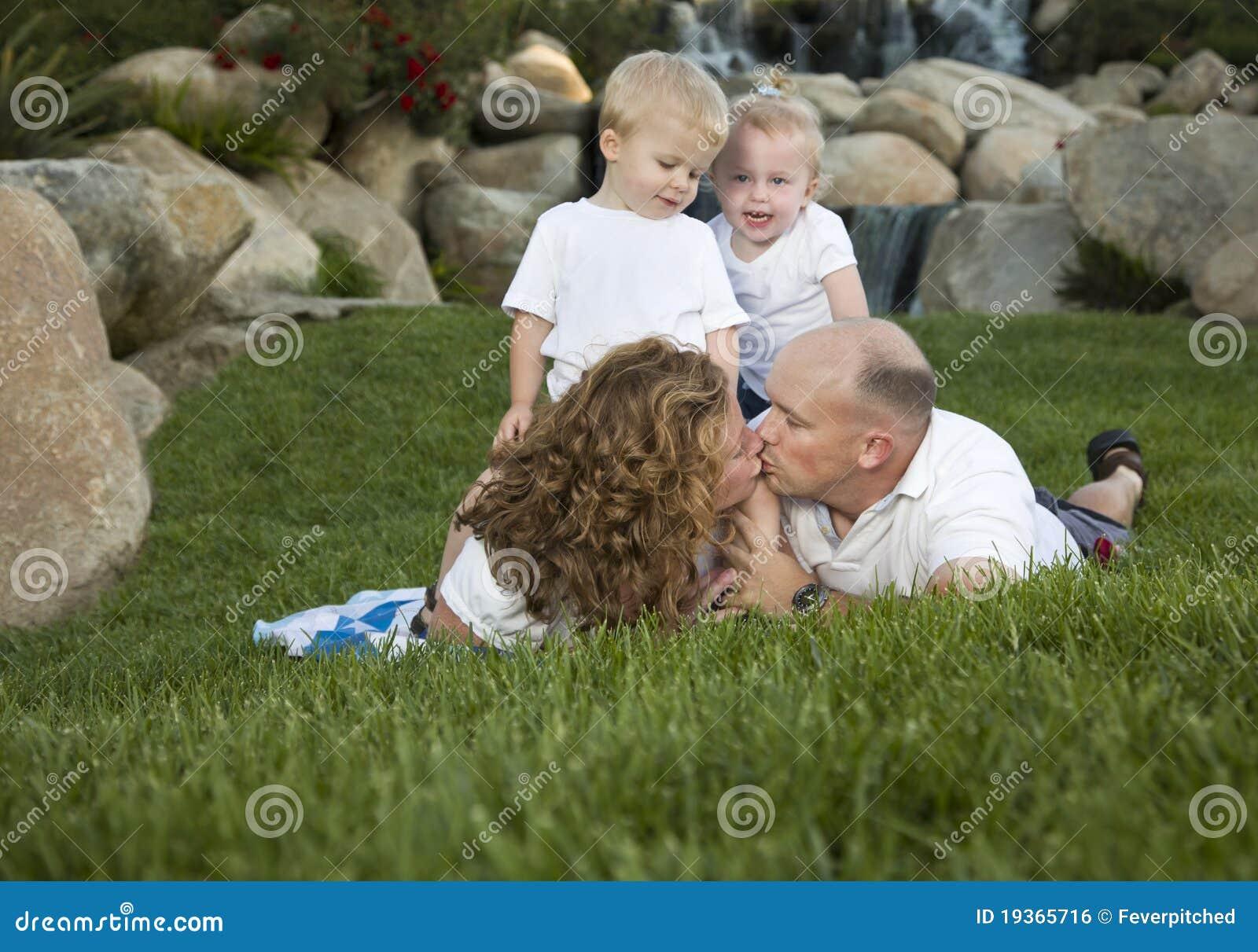 Beijo afectuoso dos pares como o olhar bonito dos gêmeos sobre