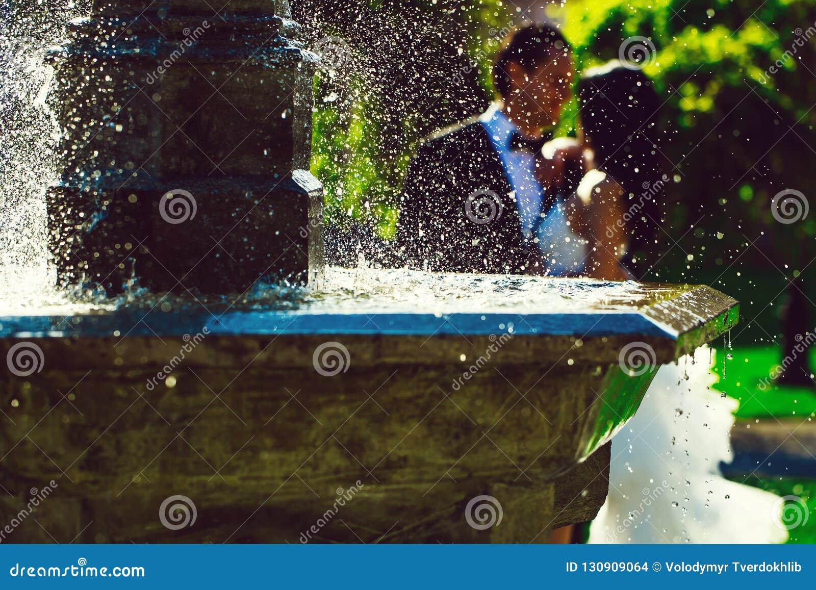 Beijo dos pares do casamento perto da água da fonte