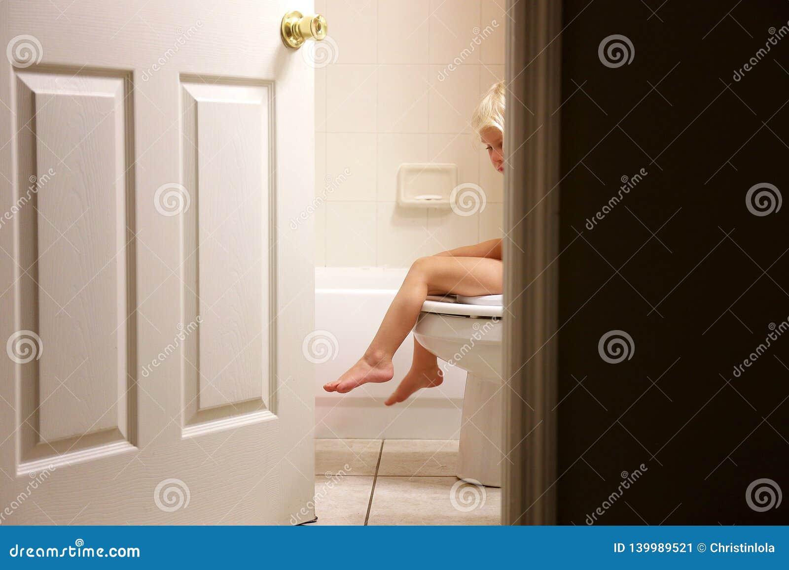 Beine des kleinen Kleinkind-Kindes, das über Toilette während kinderleichtes Training im Badezimmer baumelt