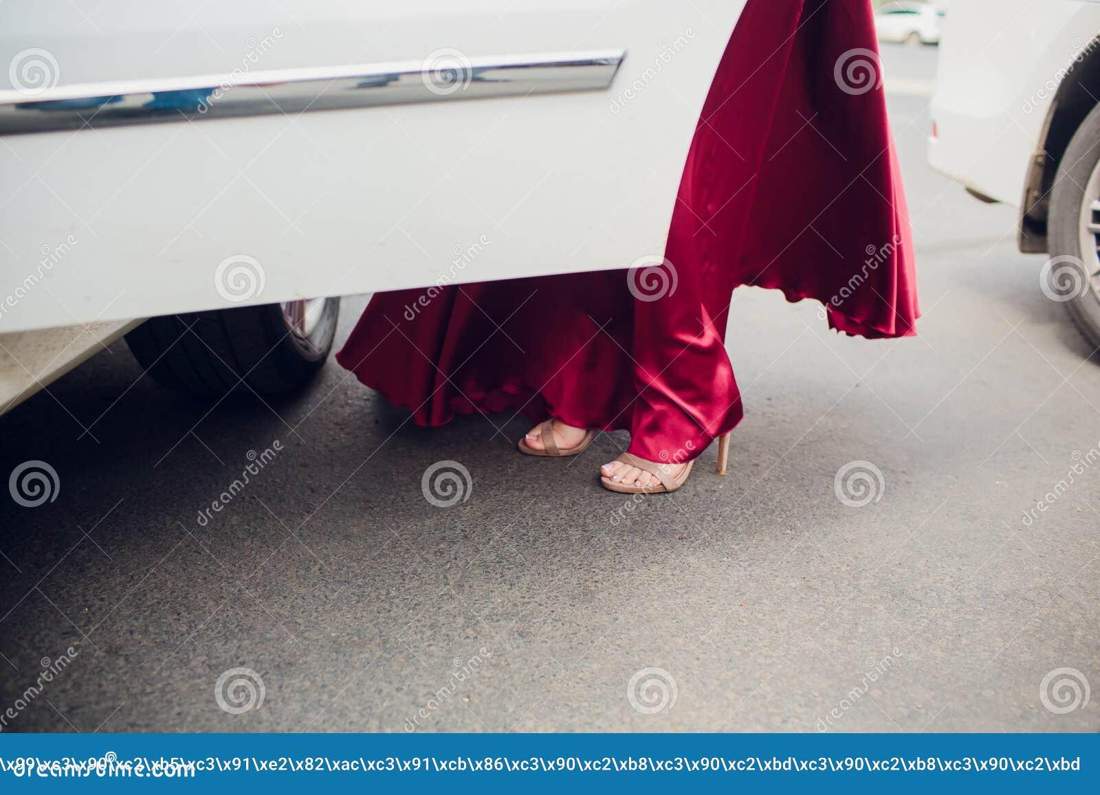 Beine des M?dchenverlassens ein altes Auto junge Frau in den Schuhen der hohen Abs?tze Fahrer?ffnungst?r des Weinleseautomobils f