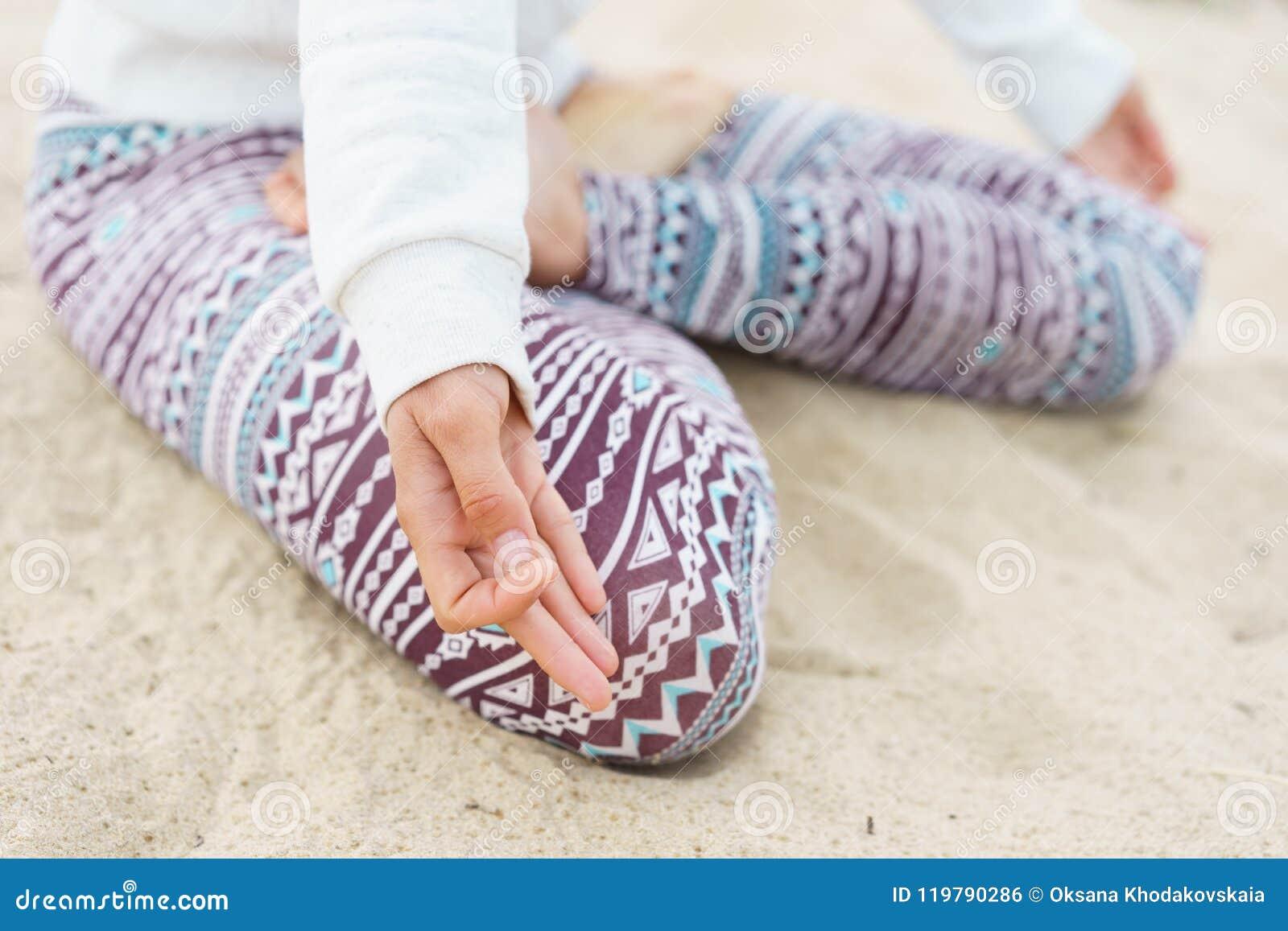 Beine, die auf dem Sand, das Mädchen im Lotussitz, Finger sitzen