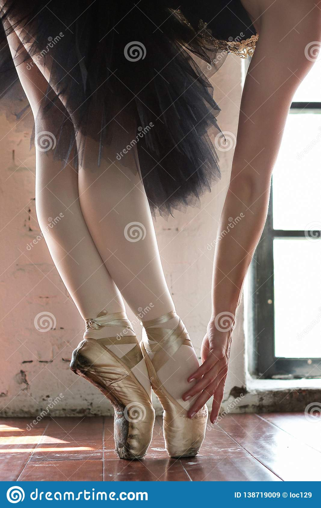 Beine einer Ballerinanahaufnahme Die Beine einer Ballerina im alten pointe Wiederholungsballerina in der Halle Konturnlicht vom F
