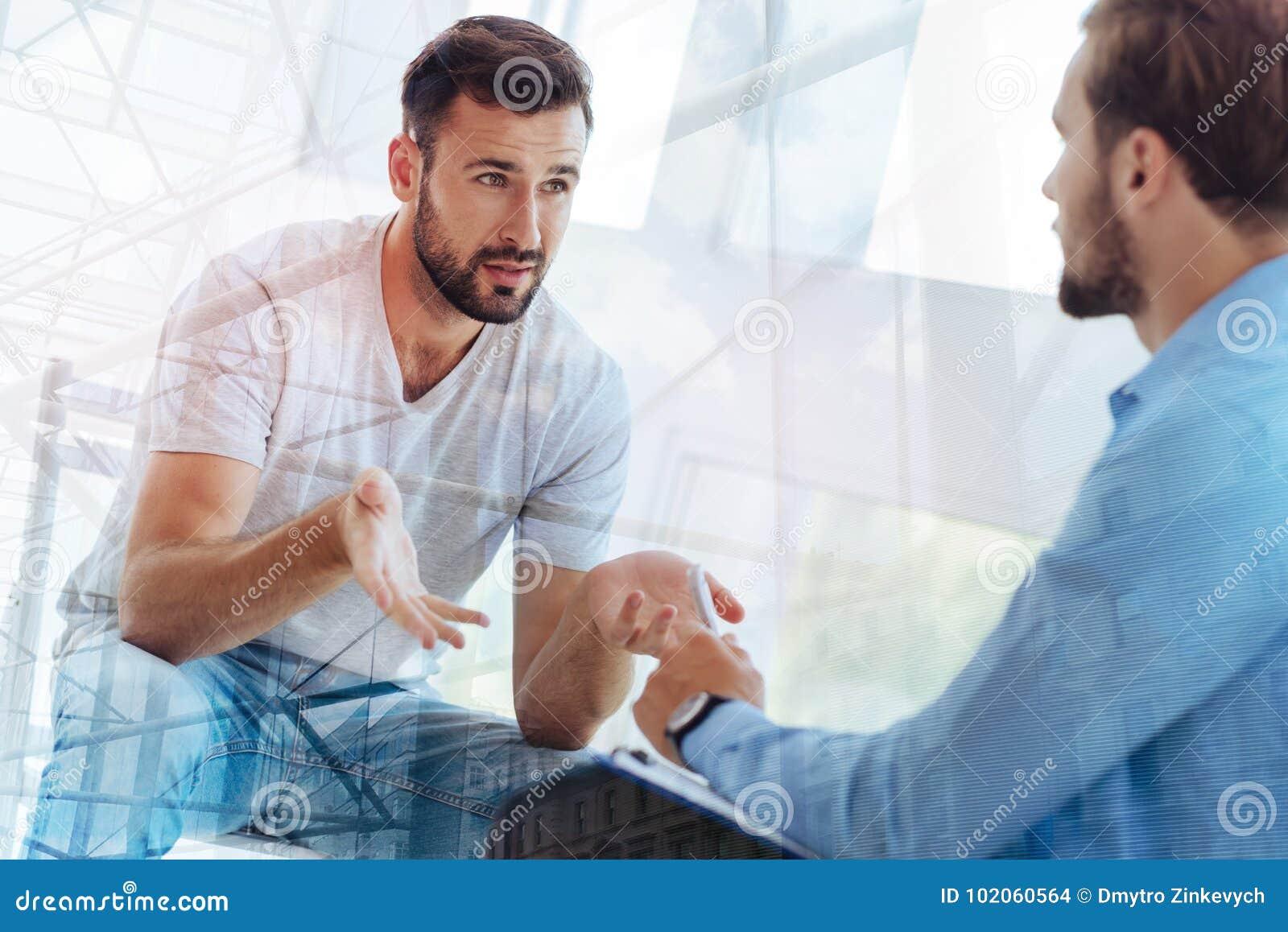 Handsome bearded man explaining his problem to psychiatrist