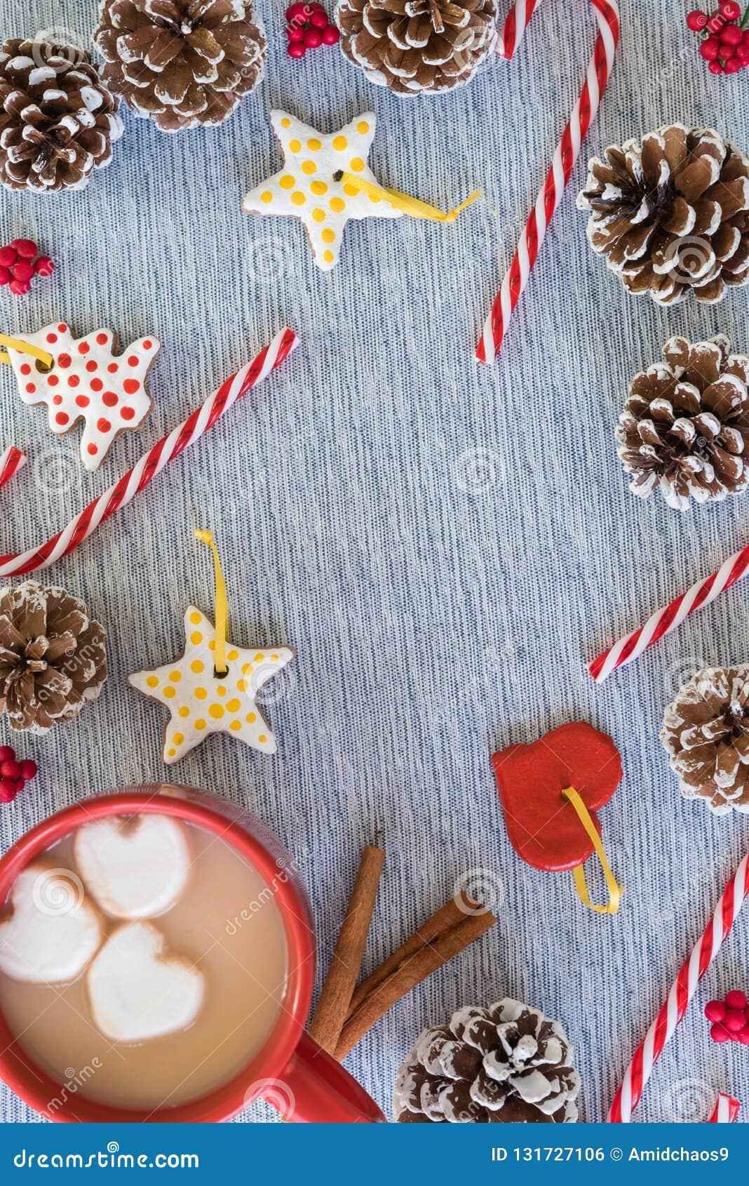 Beira colocada lisa do Natal com a caneca de cacau quente, bastões de doces, pinecones