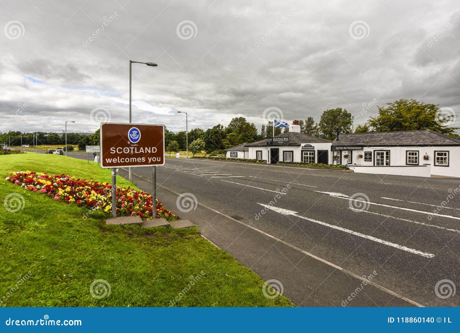 A beira a Escócia com ` Escócia do sinal dá-lhe boas-vindas `, na estrada em Grâ Bretanha