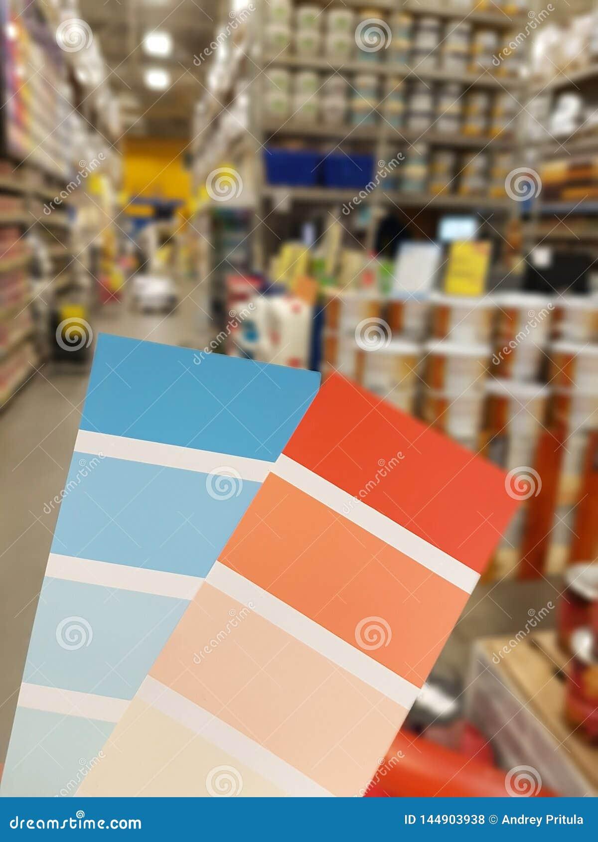 Beispielfarbenblau und -orange auf dem Hintergrund von Dosen Farbe