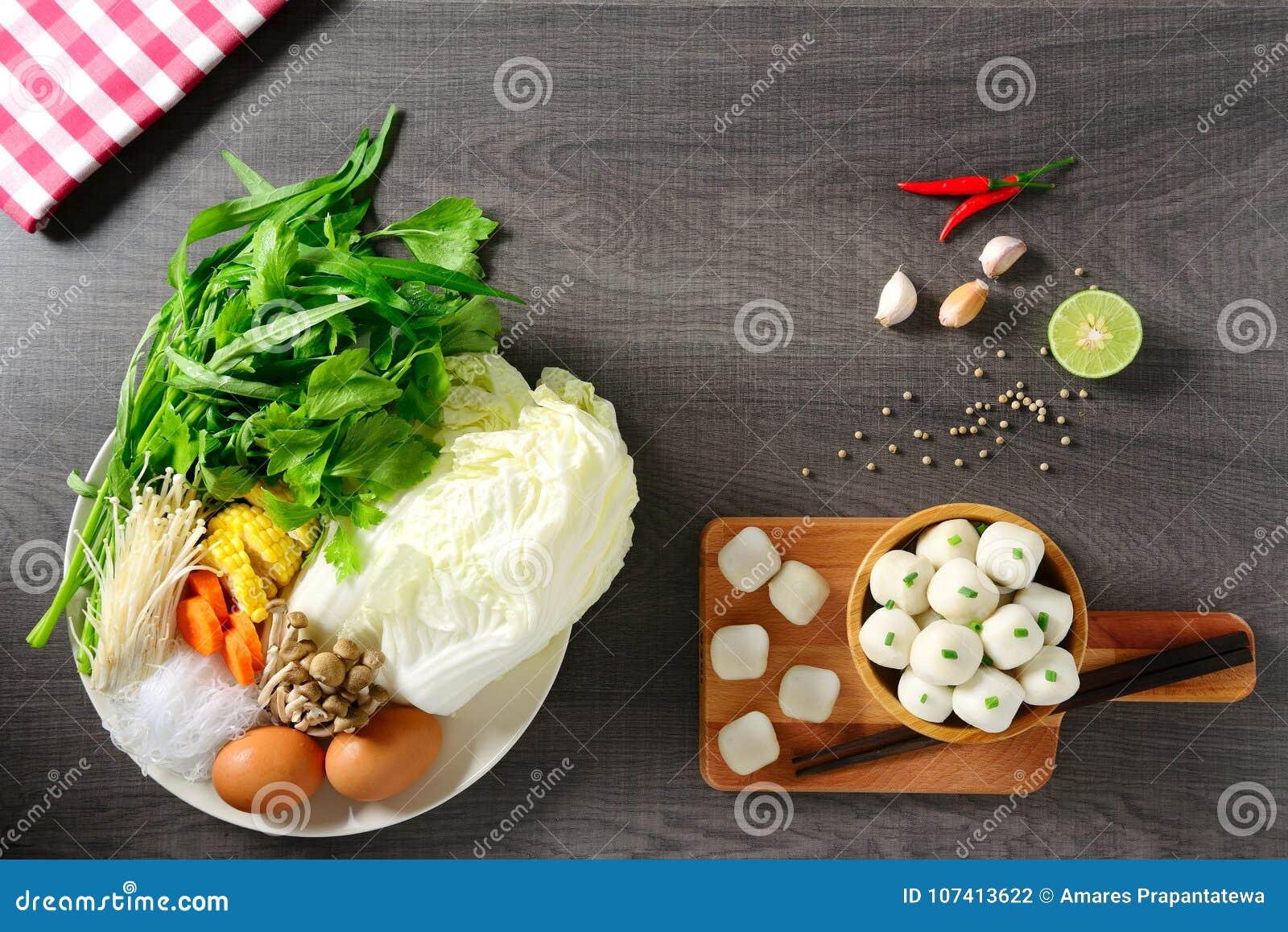 Beiträge zu thailändischem Lebensmittel, Kalk, Paprika, Knoblauch und verschiedenes Gemüse, zwei Eier auf weißem Teller und Fisch