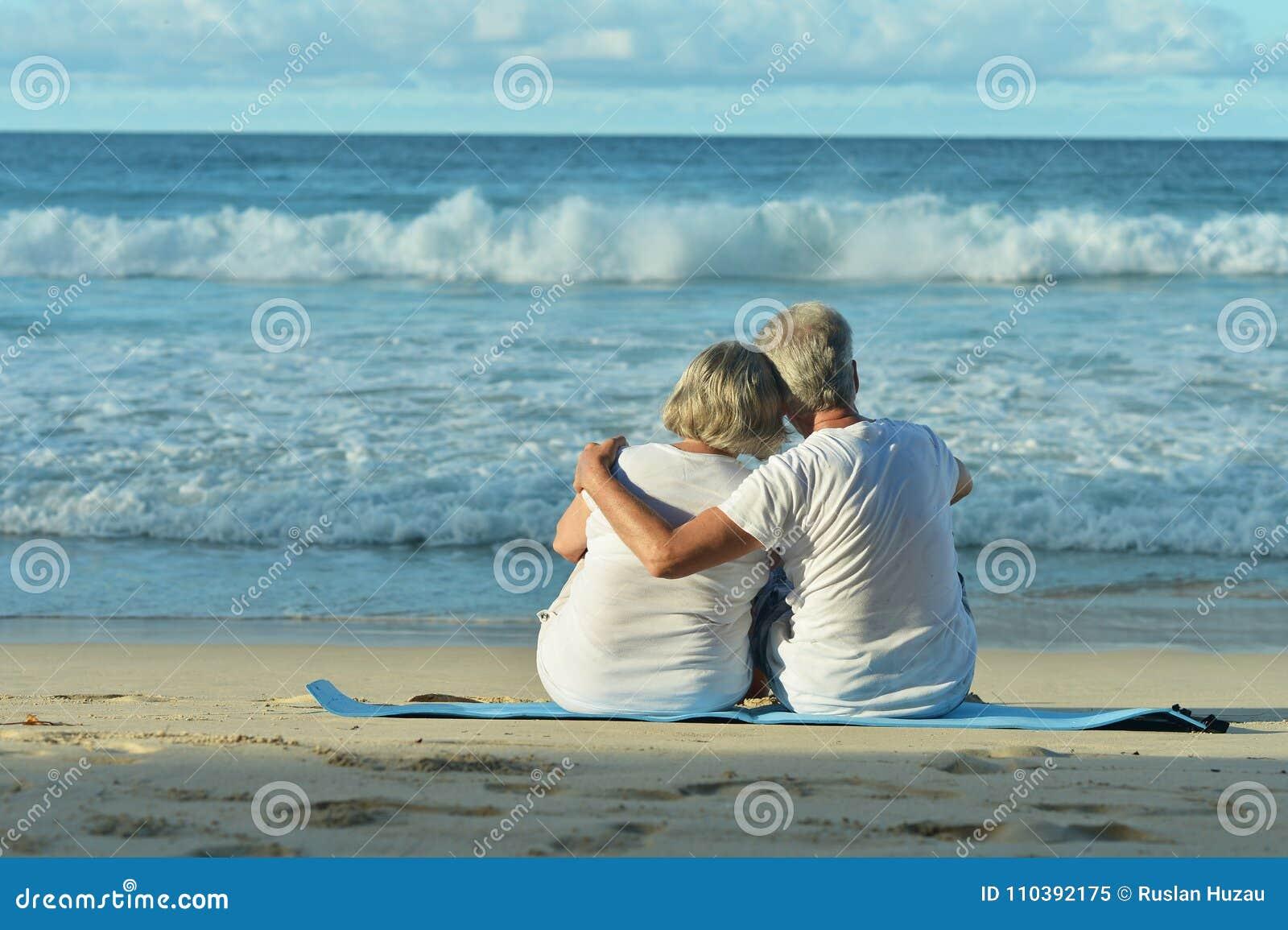 Bejaard paar die op strand lopen
