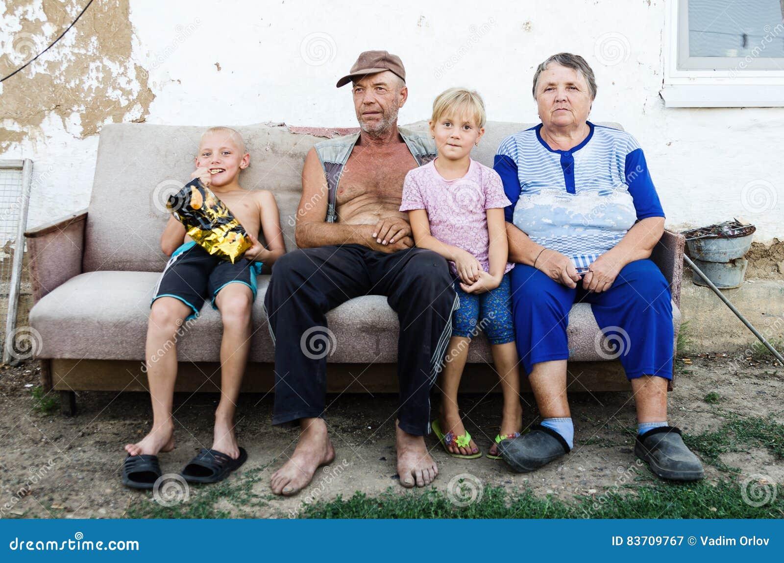 Bejaard paar met hun kleinkinderen in de werf van een dorpshuis