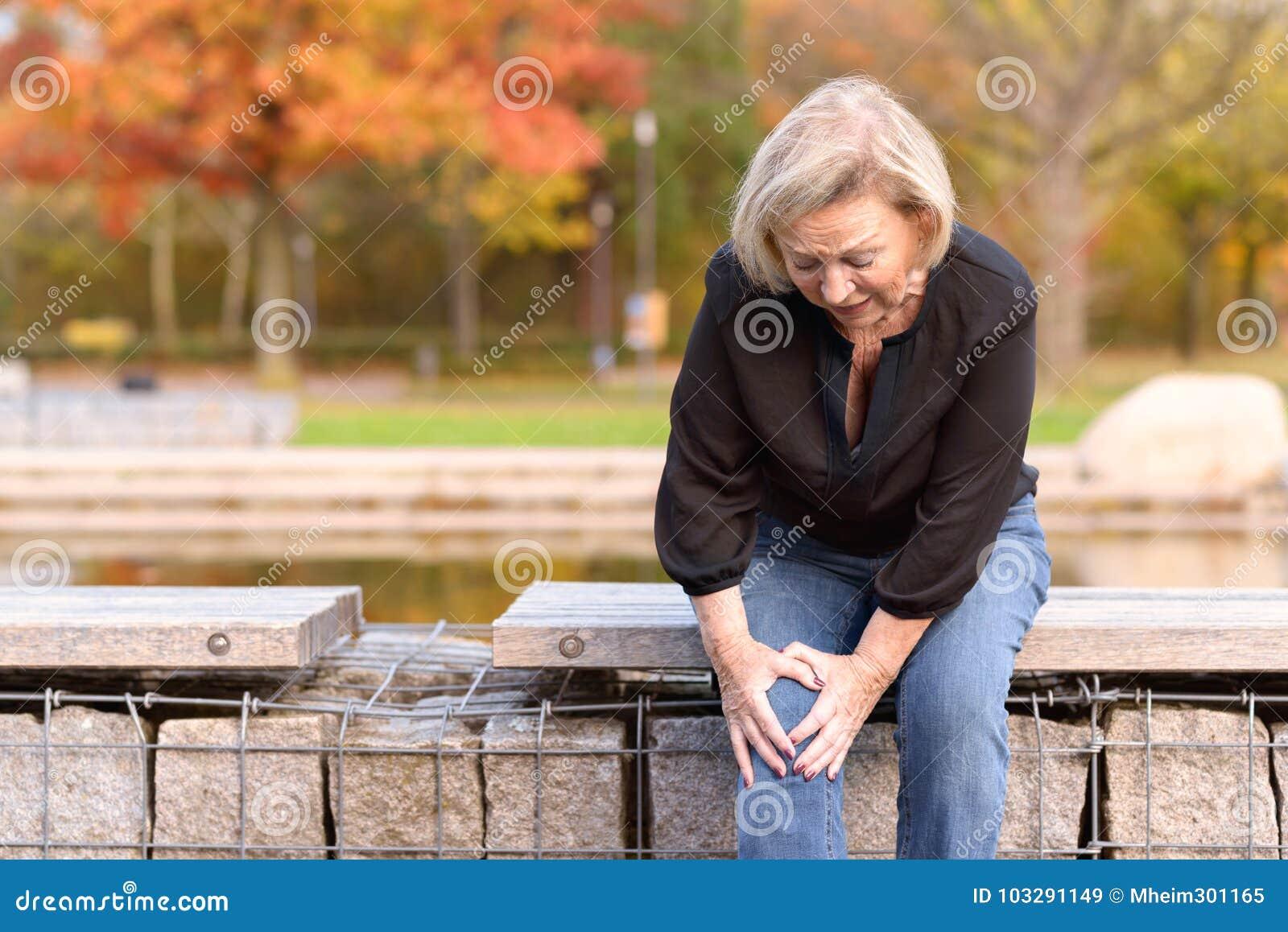 Bejaarde dame die haar knie in pijn grijpen