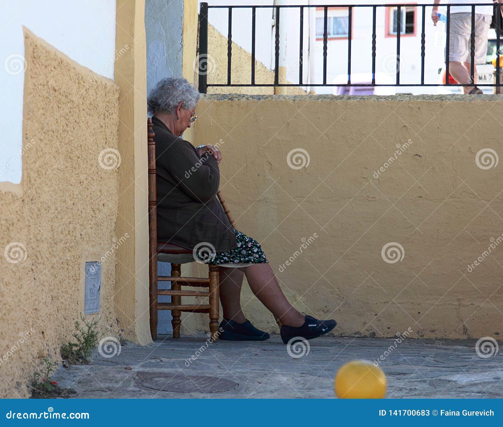 Bejaarde dame die op de stoel buiten haar huis in Ronda rusten