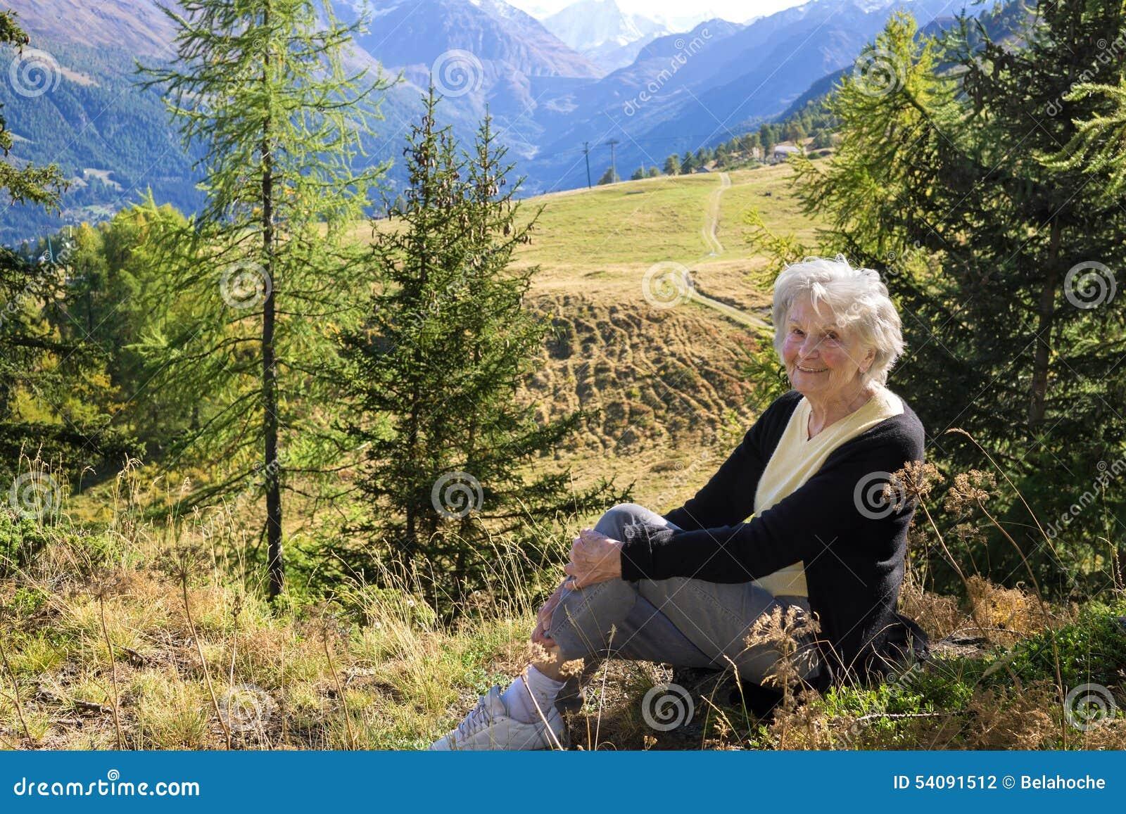 Bejaarde dame die van een vakantie in de bergen genieten