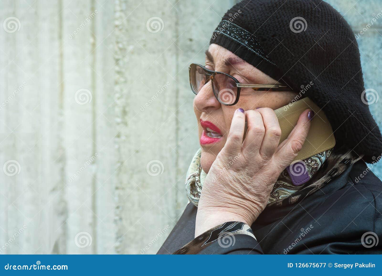 Bejaarde die met heldere make-up op de telefoon in openlucht spreken